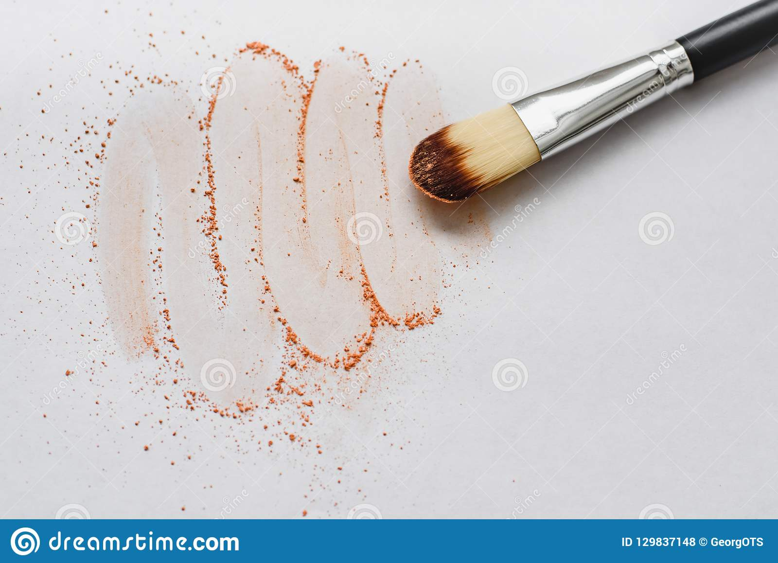Makeup brush with beige powder isolated on white background. Makeup artist tool.