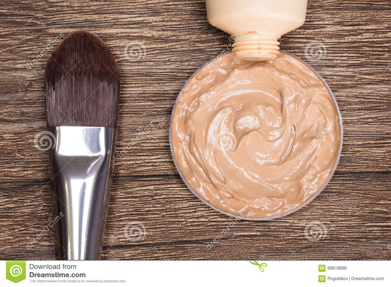 Makeup brush with liquid foundation squeezed out of tube