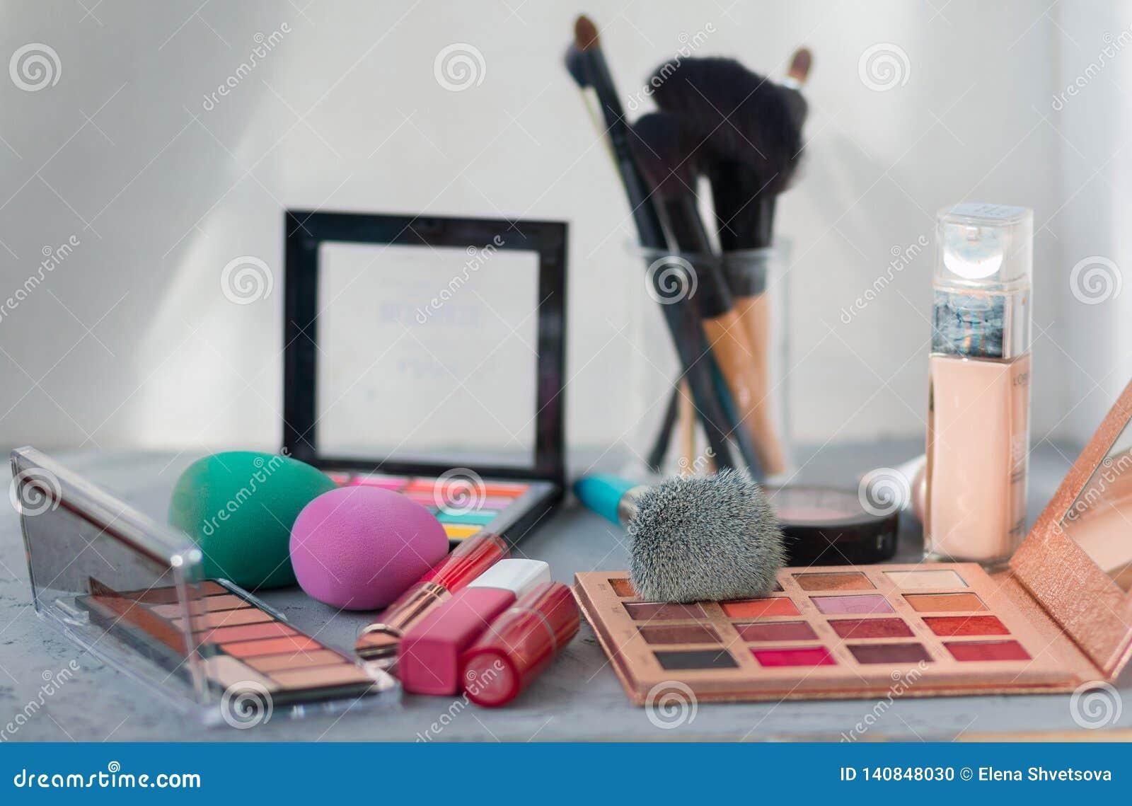 Makeupborste och skönhetsmedel på den gråa tabellen