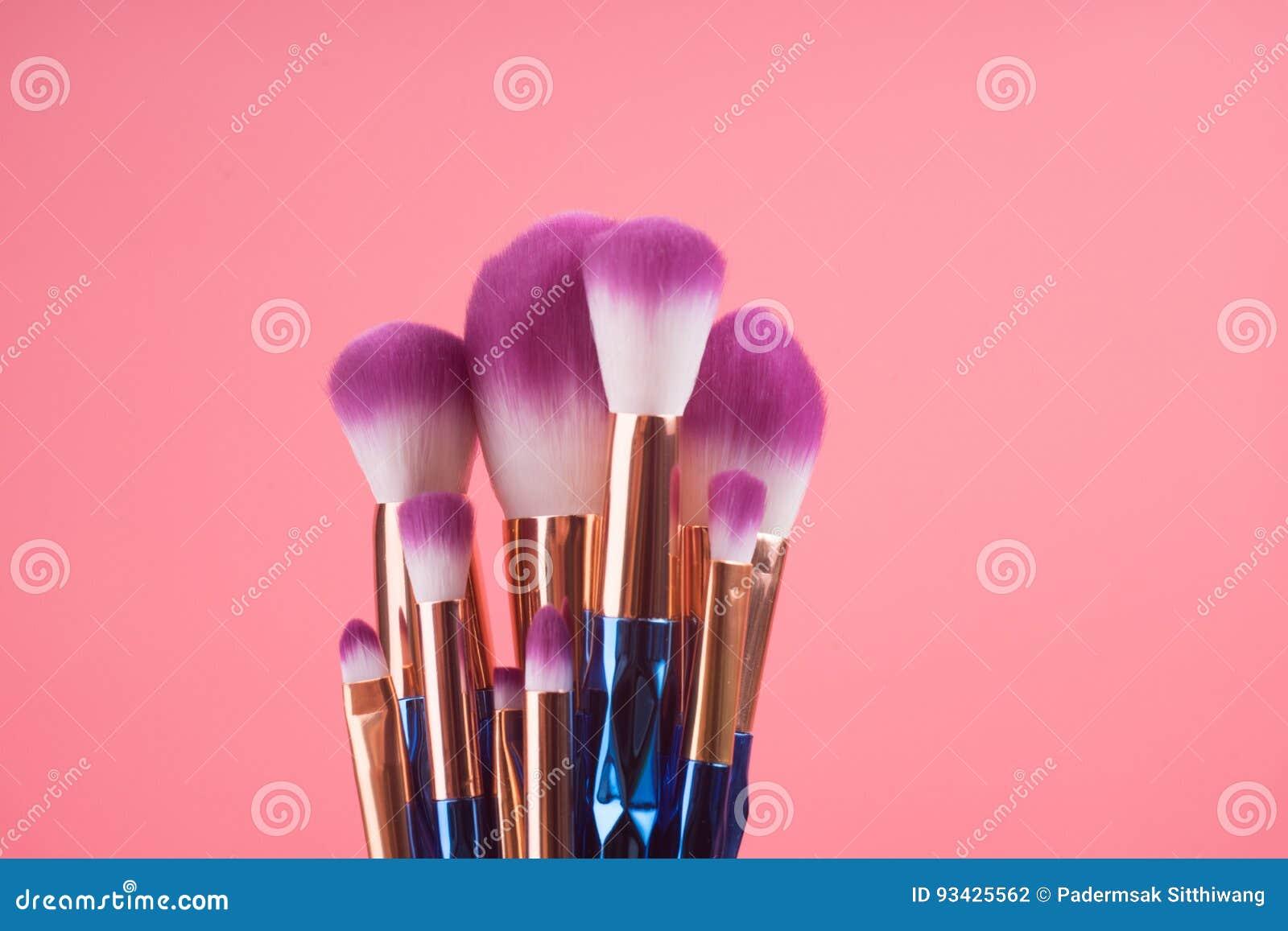 Makeupborsteuppsättning på röd rosa pastellfärgad bakgrund