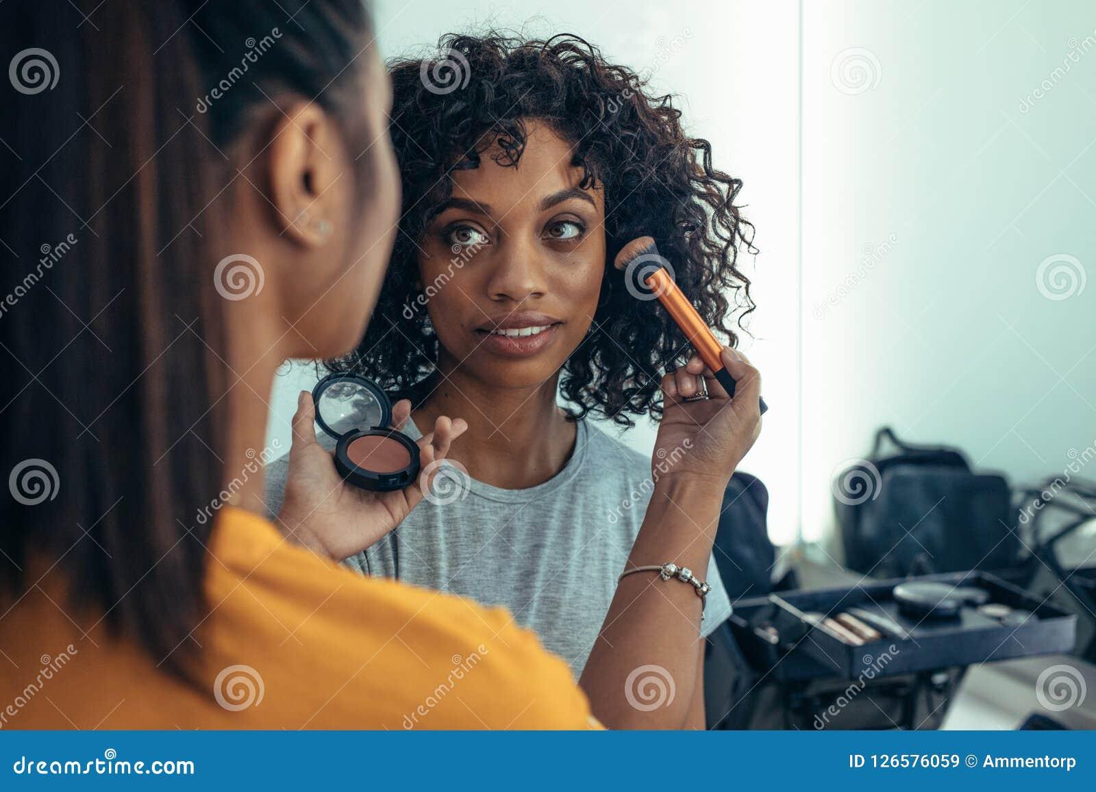 Makeupkonstnär som arbetar på framsida av en modell