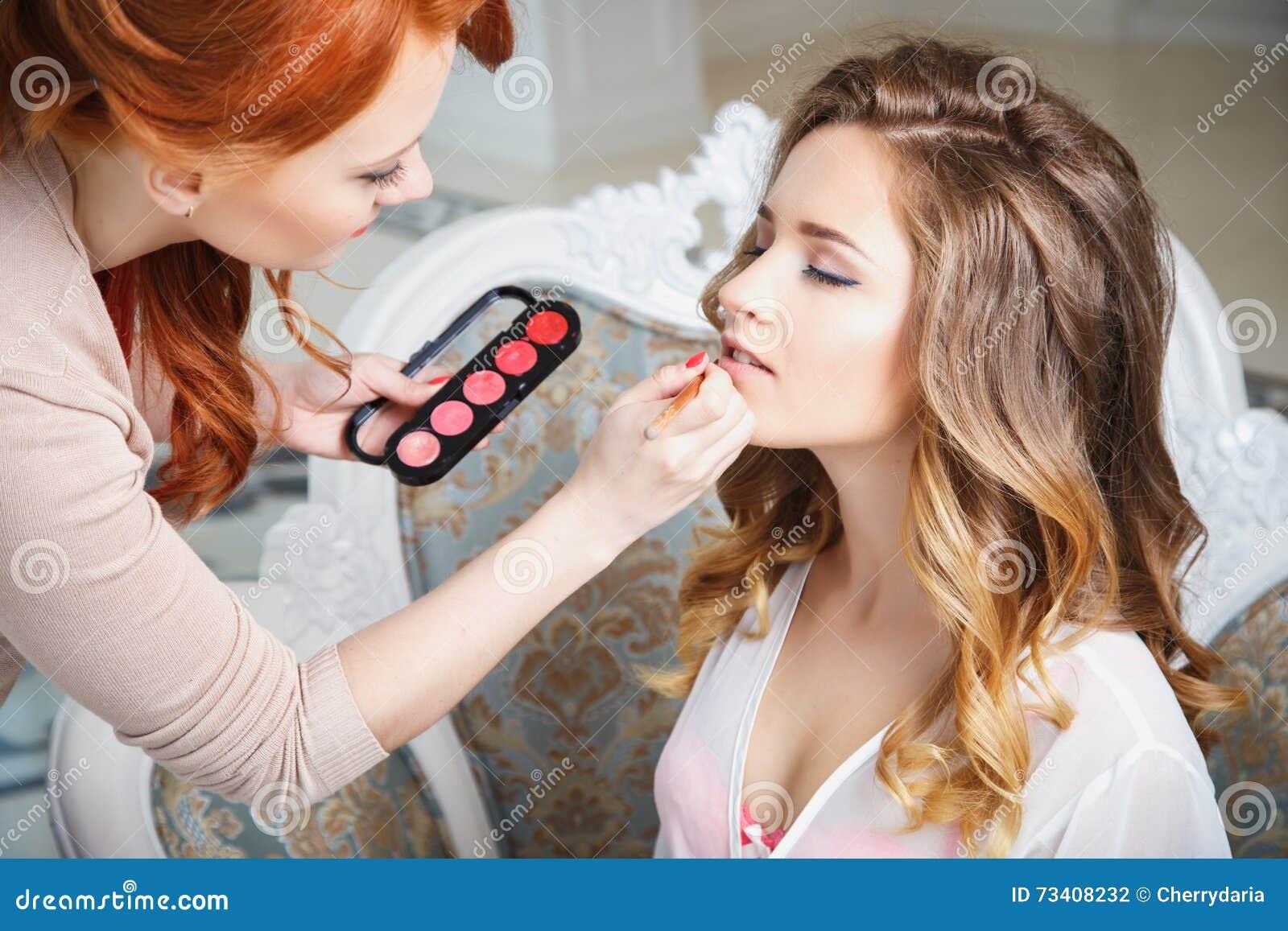 Makeupkonstnär som förbereder bruden för bröllopet i en morgon