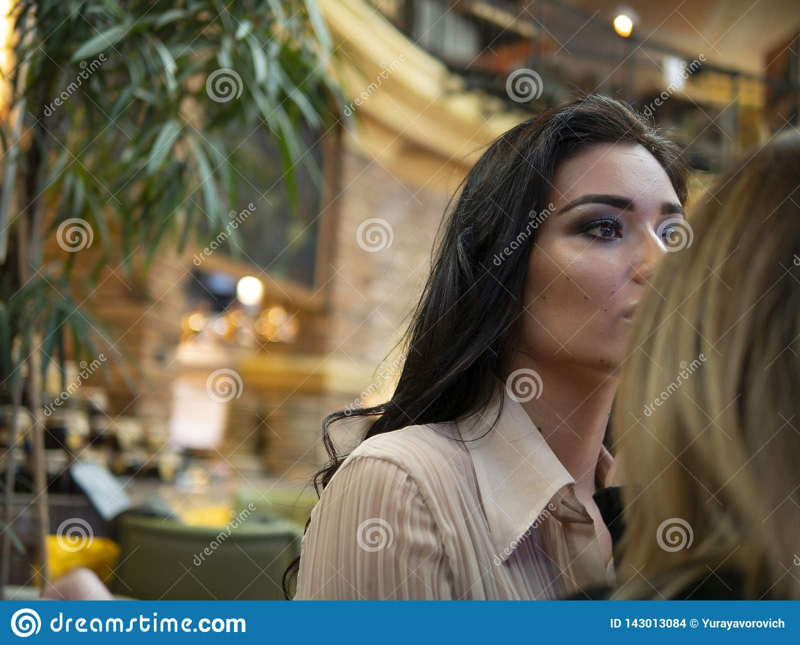 Makeupkonstnären utgör till den härliga unga kvinnan inomhus yrkesmässiga målarfärgkanter med läppstift