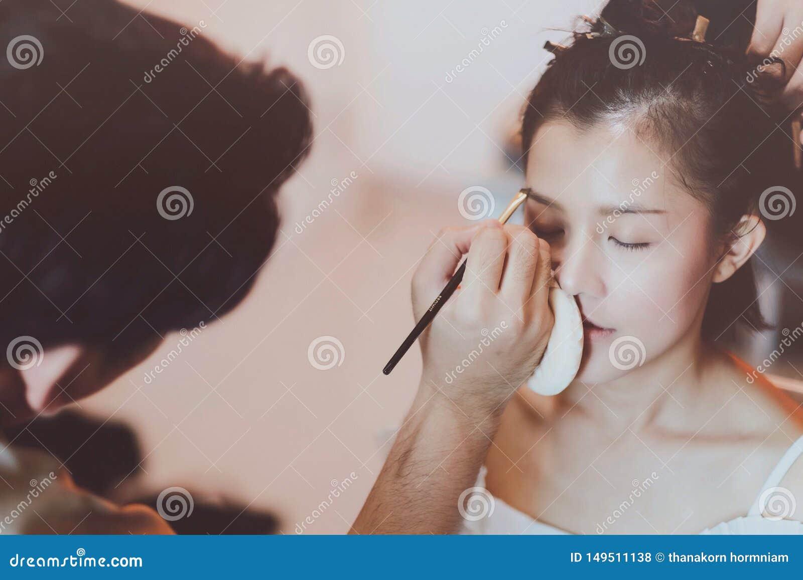 Makeupkonstn?r som arbetar p? h?rlig asiatisk modell