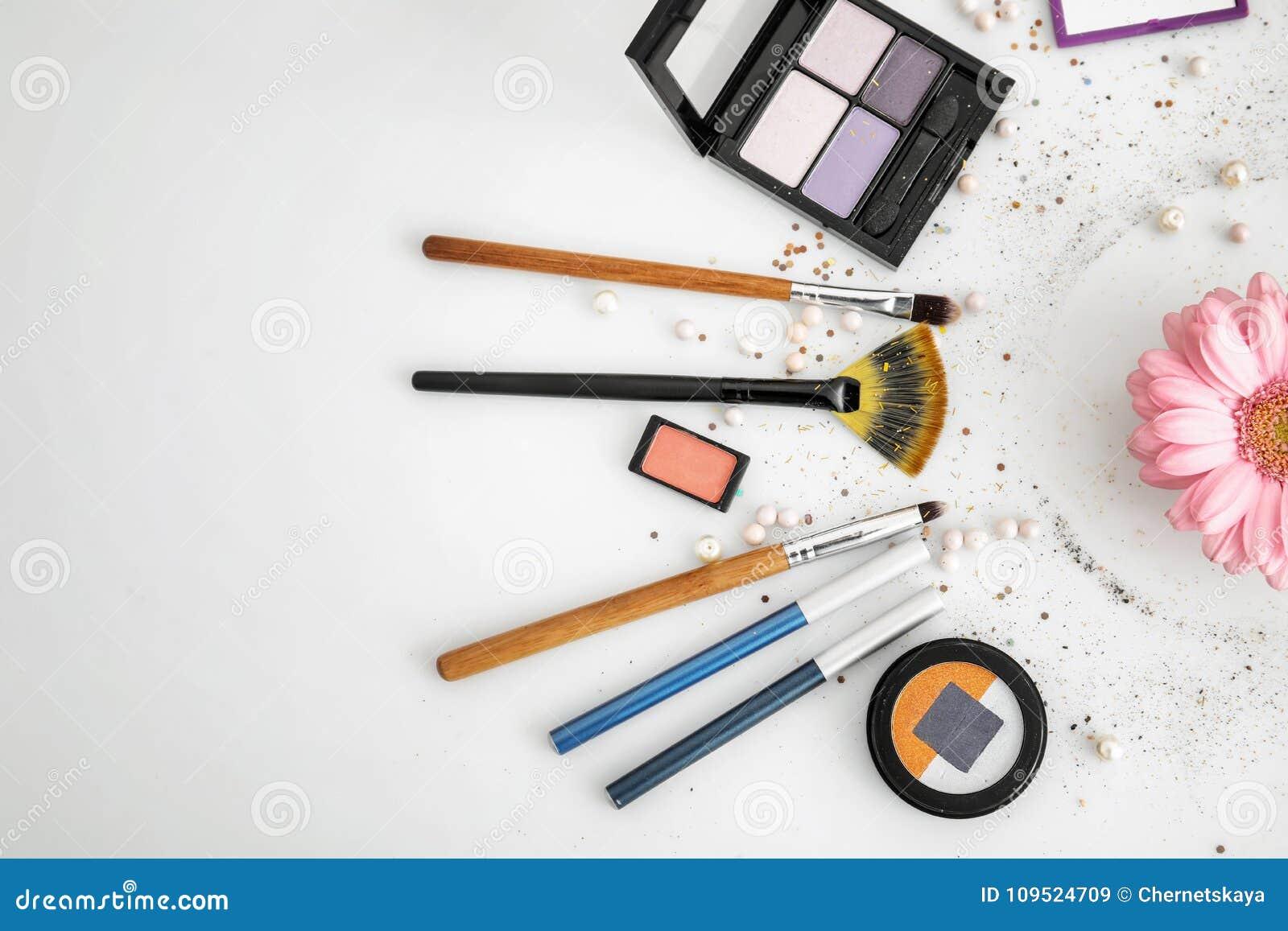 Makeupobjekt och blomma på vit bakgrund