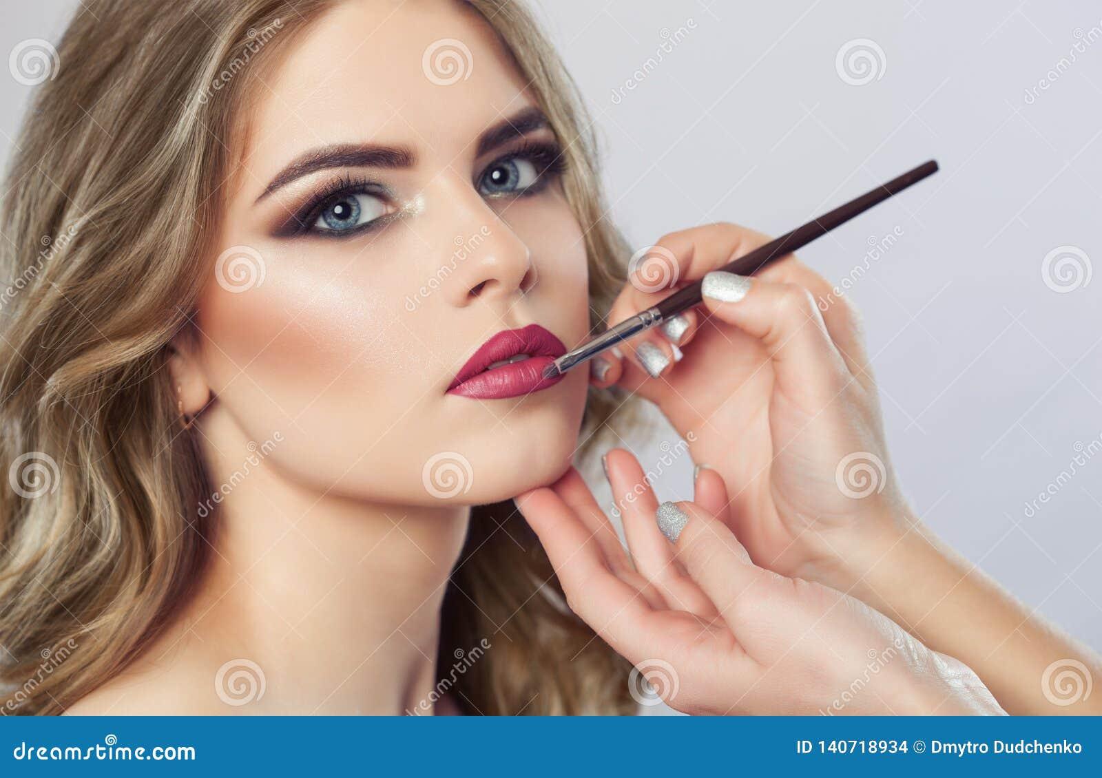 Makijażu artysta maluje wargi piękna kobieta, uzupełnia makijaż w piękno salonie