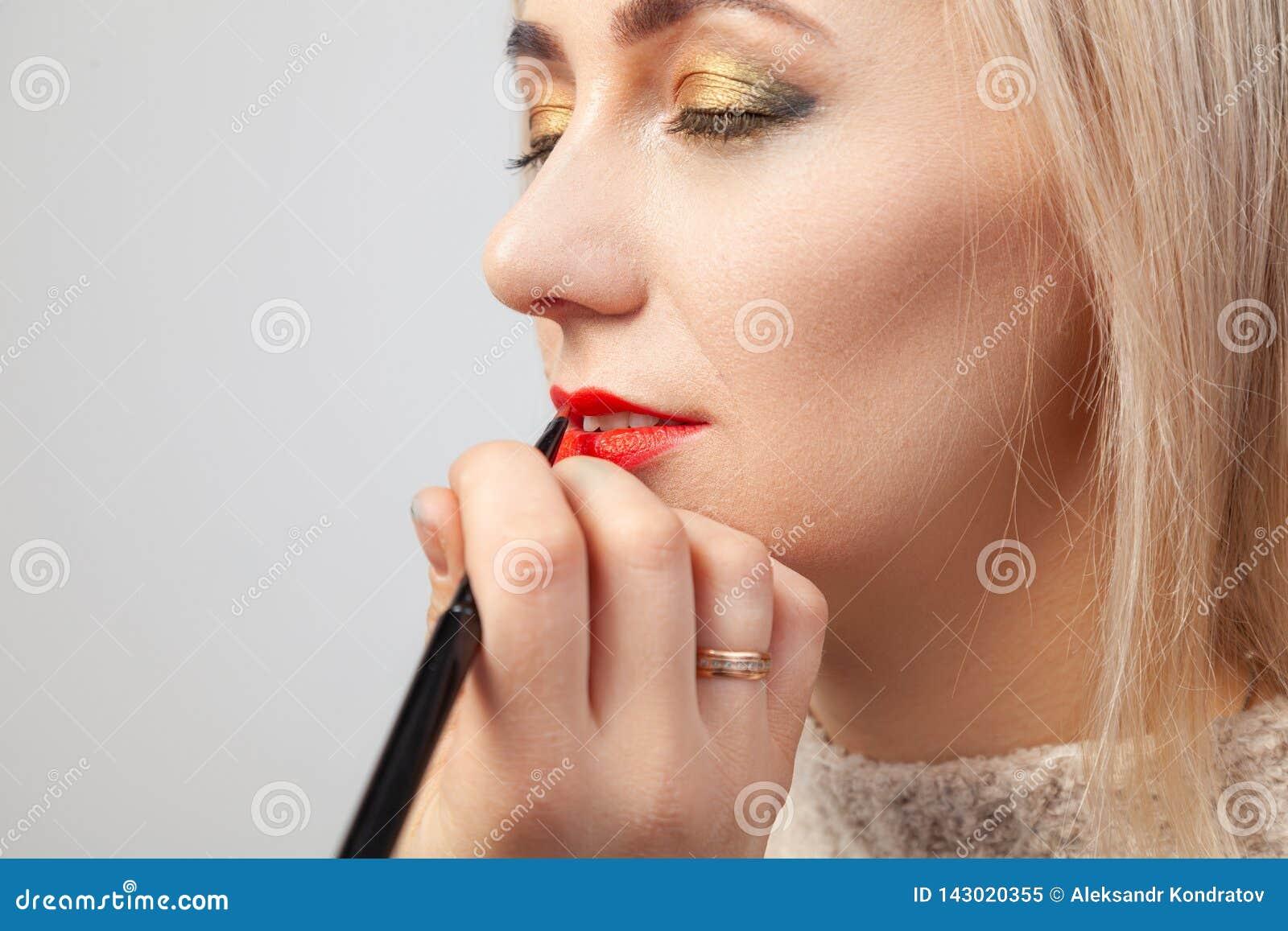 Makijażu artysta w studiu narzuca luksusowego orientalnego makijaż młodej dziewczyny blondynka, w czyj ręce muśnięcie trzyma