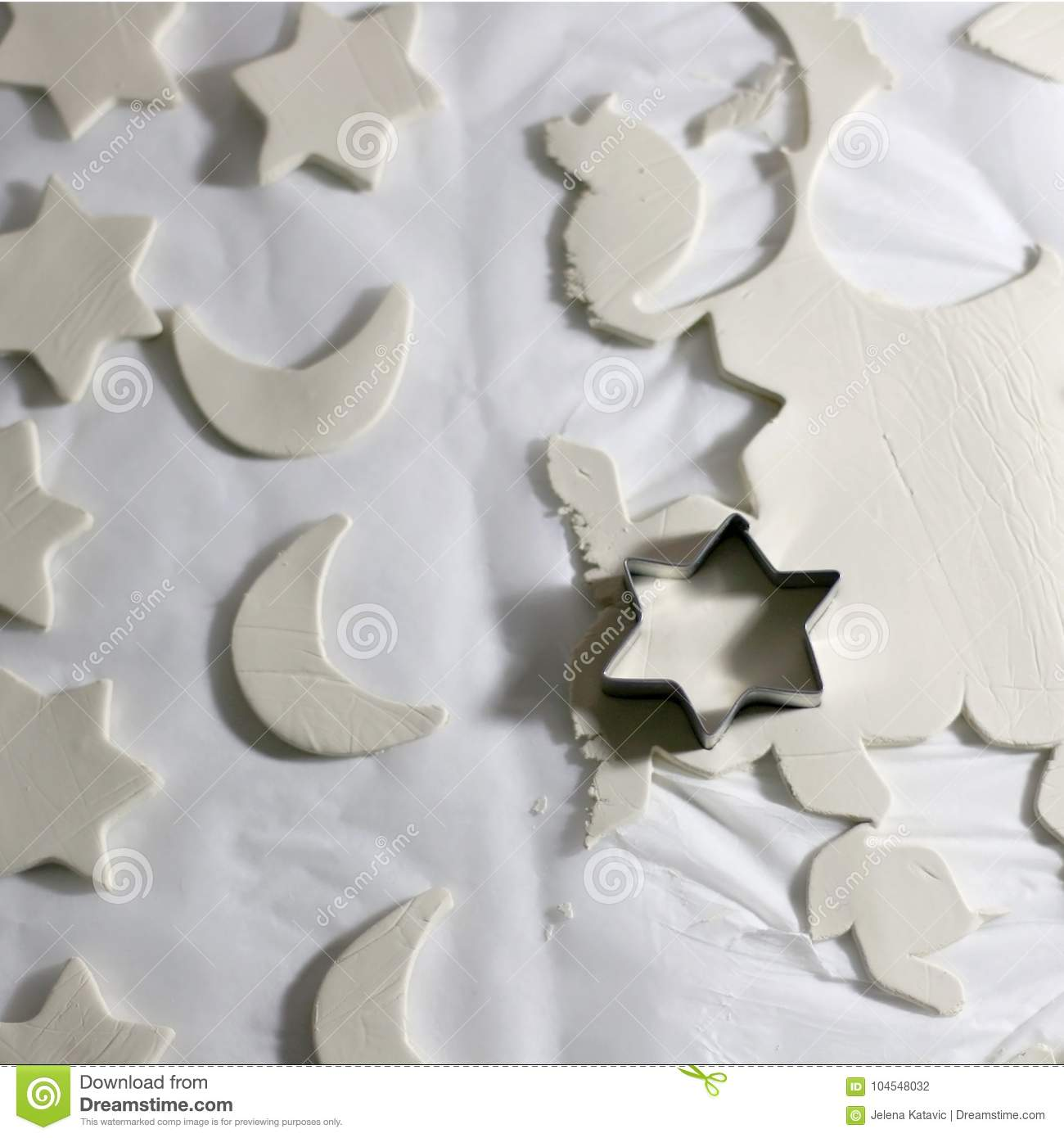 Making homemade Christmas decorations with white clay and cookie cutters. Selective focus.