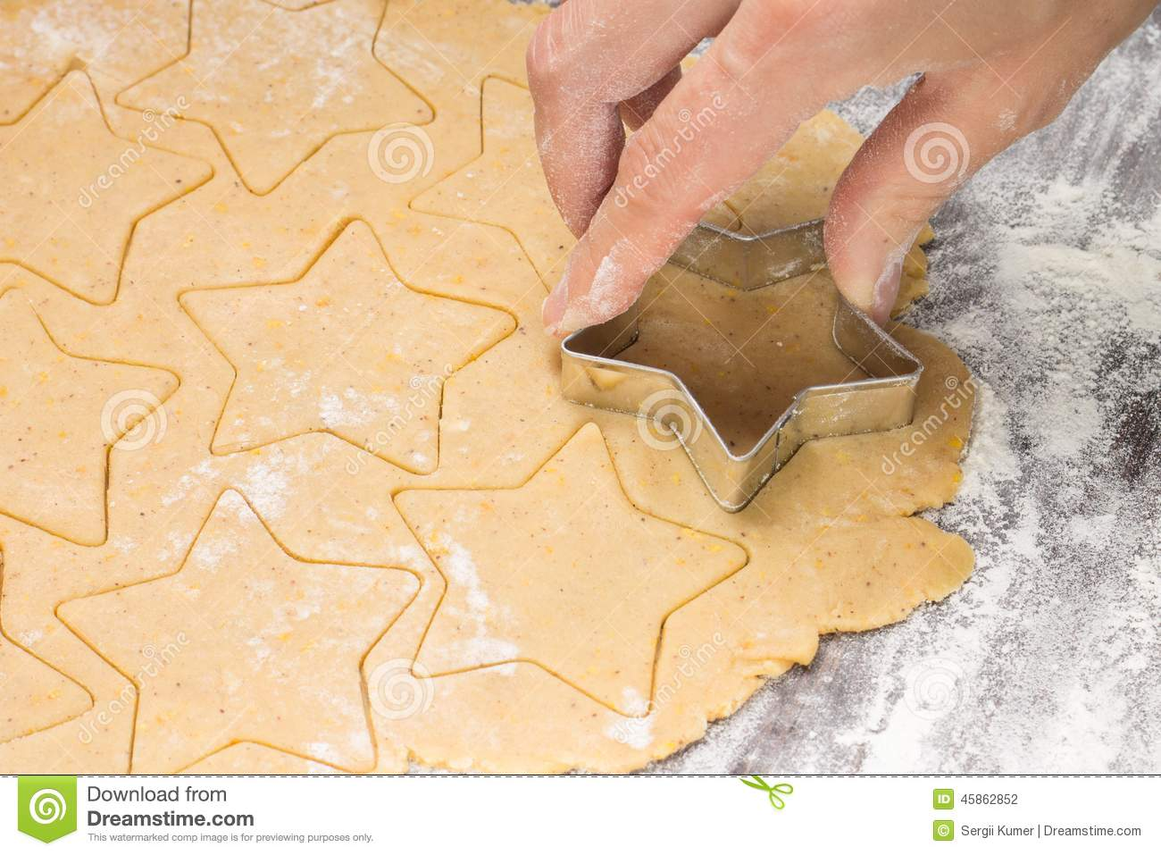 Making ginger bread christmas cookies with metal cutter. Ginger dough and flour