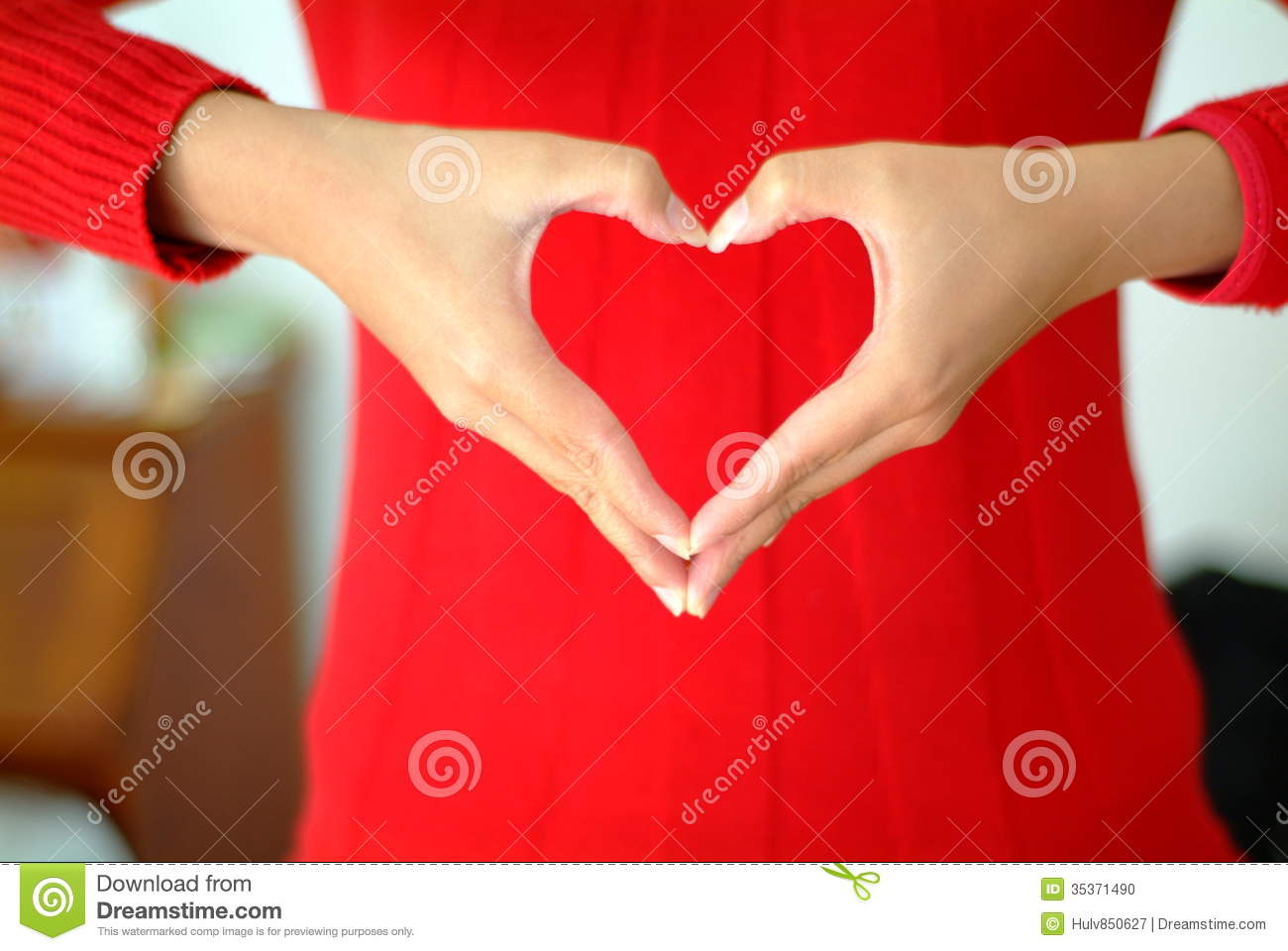 Close up of single woman s hands making a heart shape
