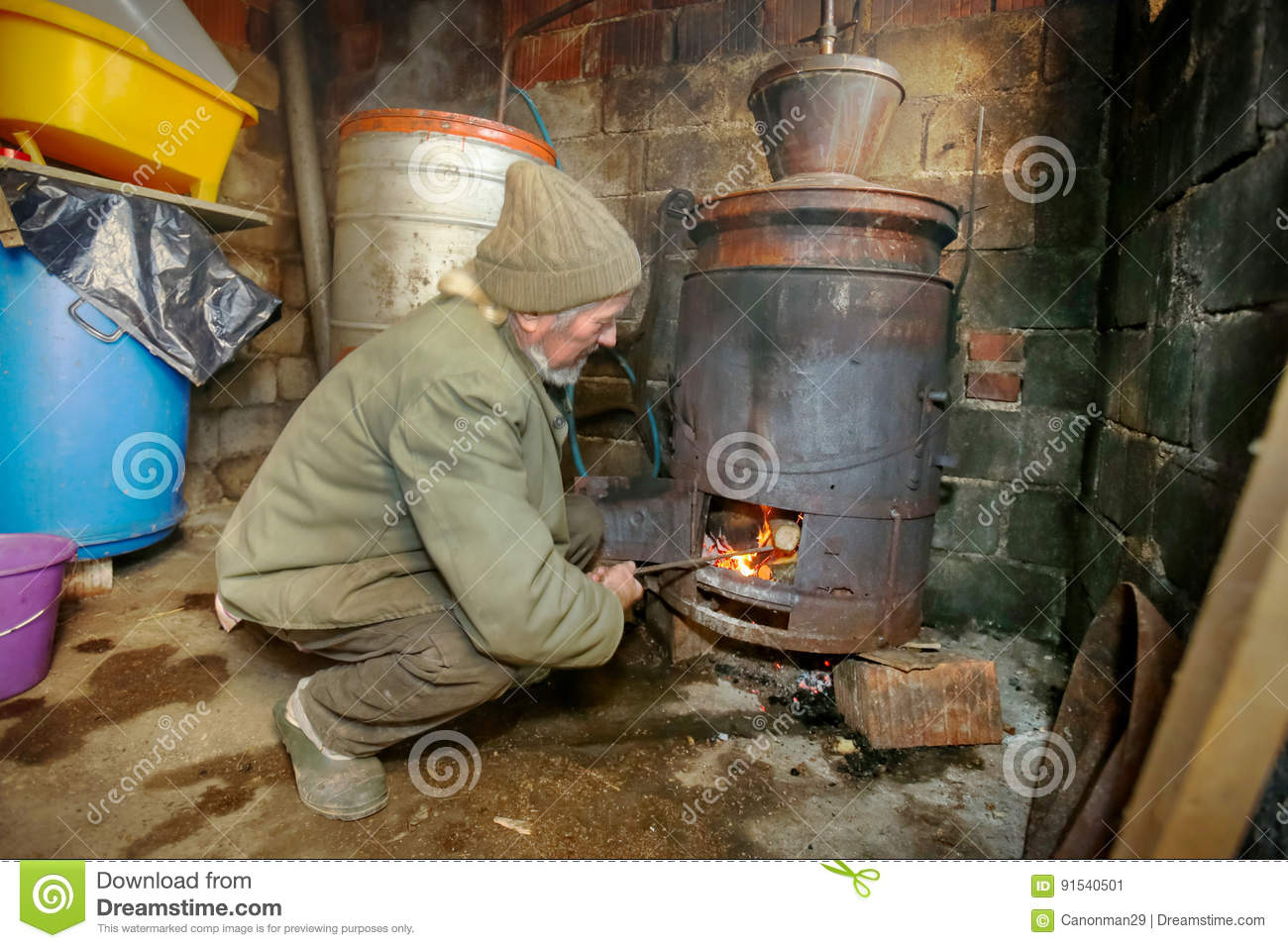 An older man making homemade brandy in the boilers in his shed.