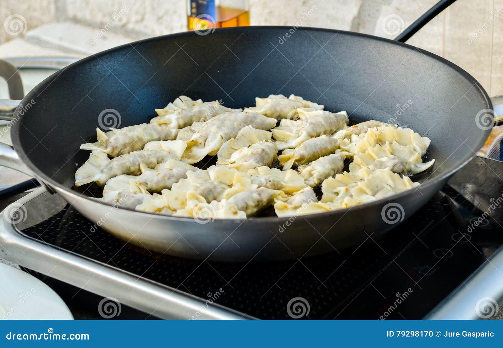 making homemade gyoza japanese dumplings in frying pan stock