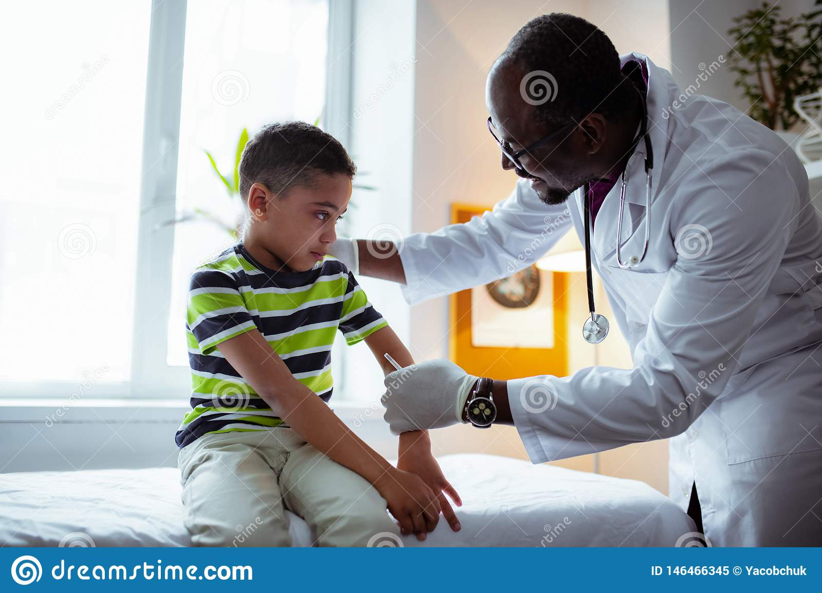 Pleasant pediatrician making injection for cute little boy