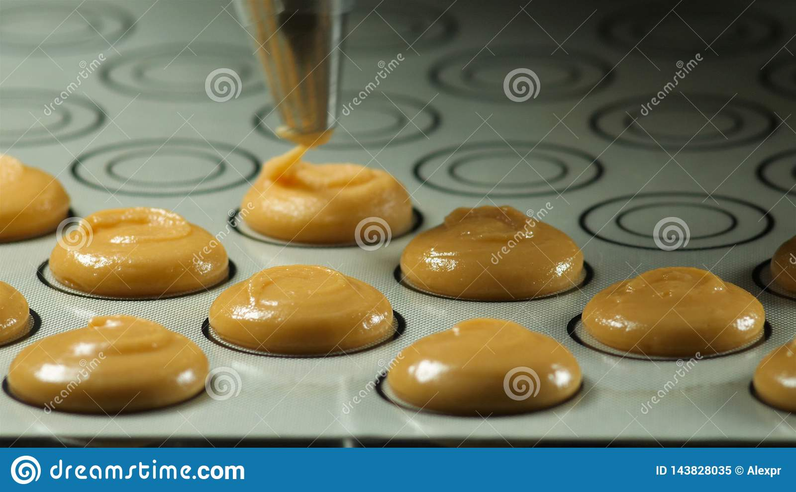 Making macaron , french dessert, squeezing the dough form cooking bag. Food industry, mass or volume production.
