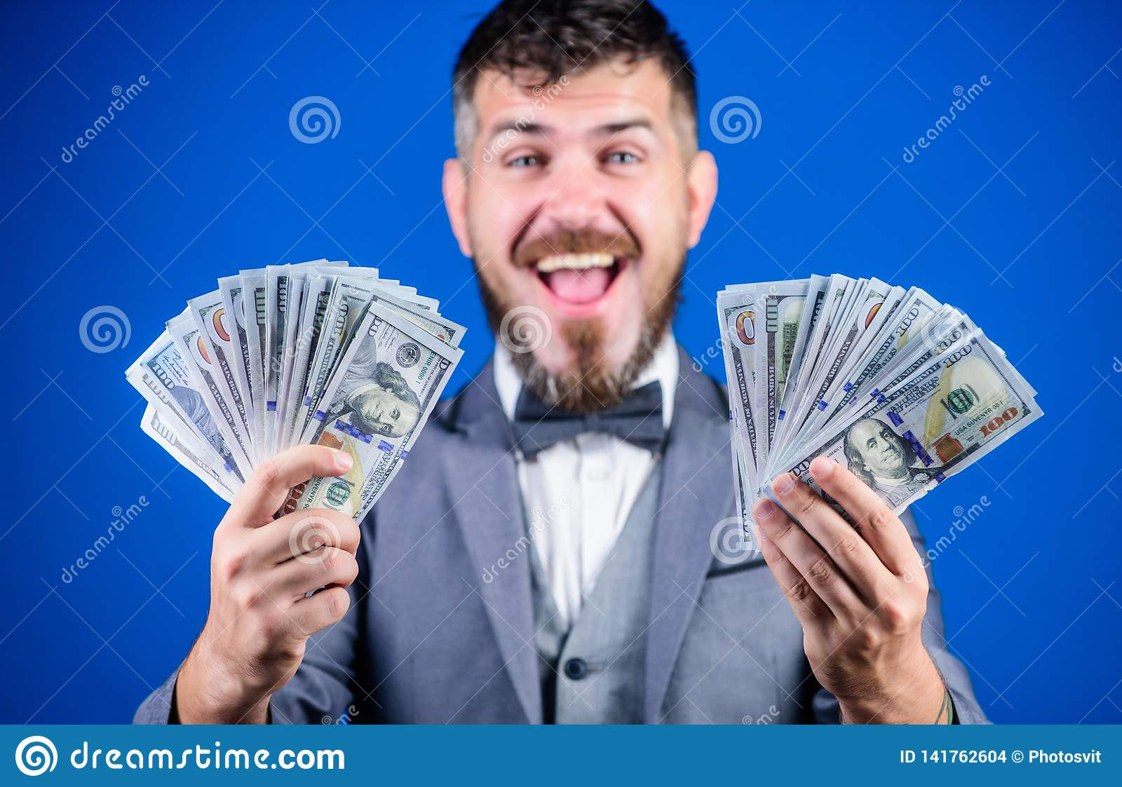 Making money with his own business. Bearded man holding cash money. Rich businessman with us dollars banknotes. Currency