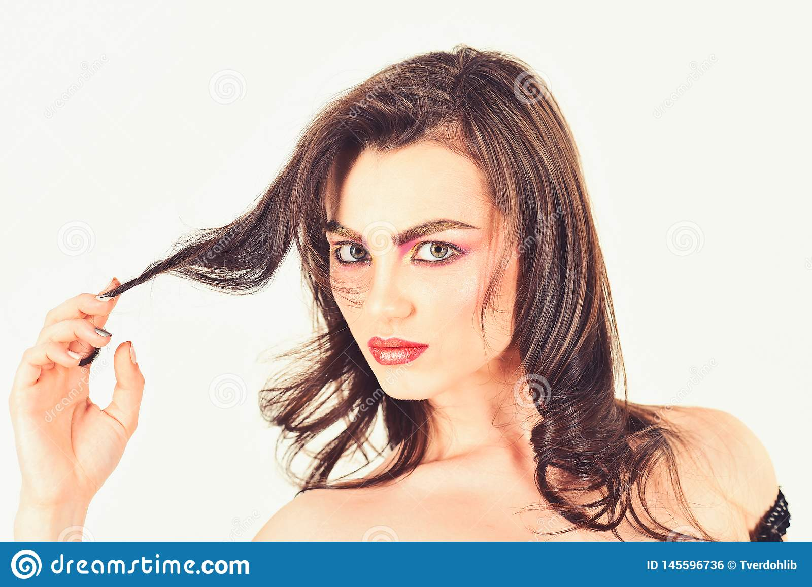 Making my hair look fabulous. Pretty woman wear long and wavy hair. woman with perfect makeup. Makeup model with