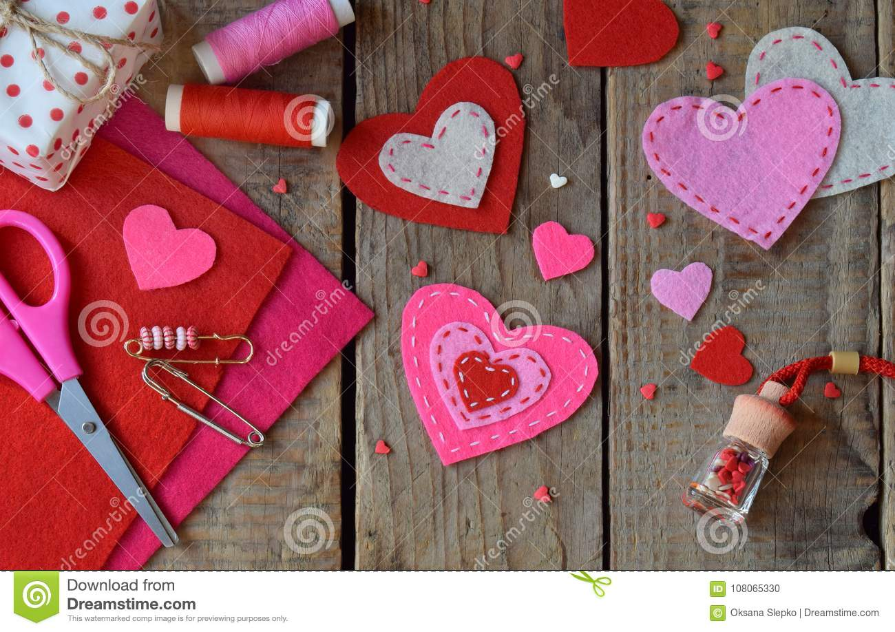 Making pink and red hearts of felt with your own hands. Valentine`s Day background. Valentine gift making, diy hobby. Children`s