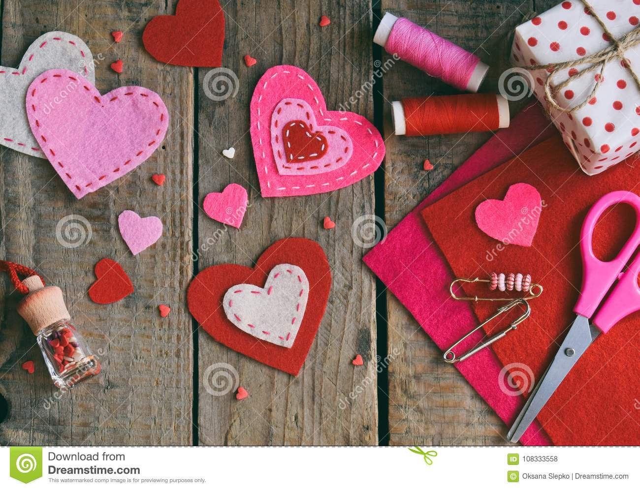 Making pink and red hearts of felt with your own hands. Valentines Day background. Valentine gift making, hobby. Childrens DIY