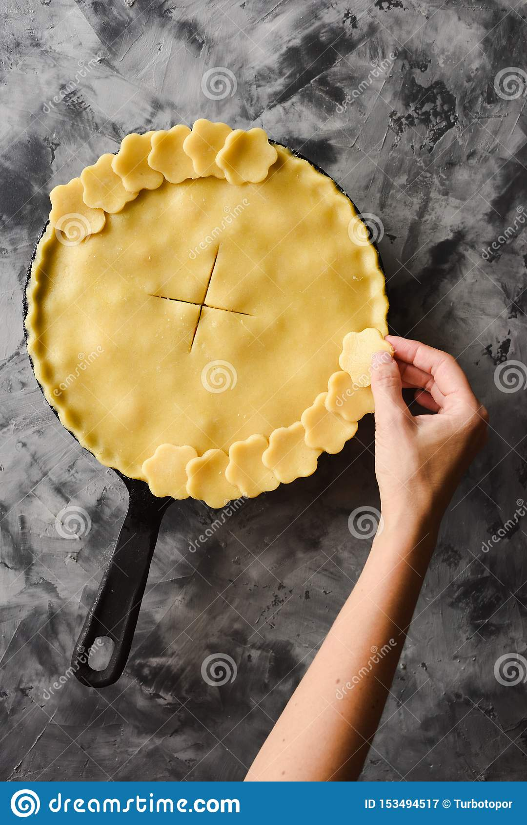 Making traditional berry pie in cast iron pan. Slender woman hand decorating crust of raw pie before baking on dark background top