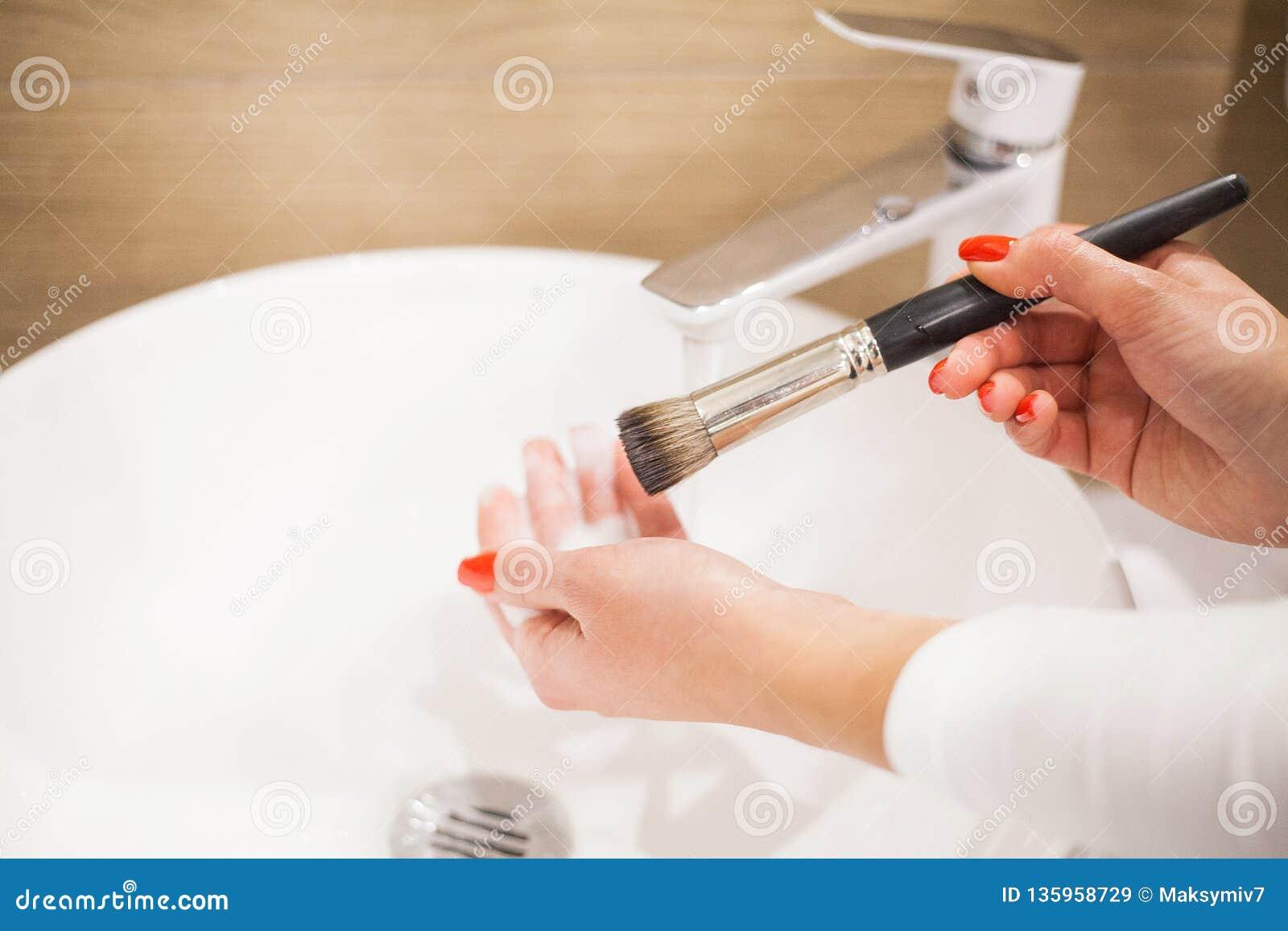 Makr επάνω στη βούρτσα Γυναίκα που πλένει τη βρώμικη βούρτσα makeup με το σαπούνι και τον αφρό στο νεροχύτη