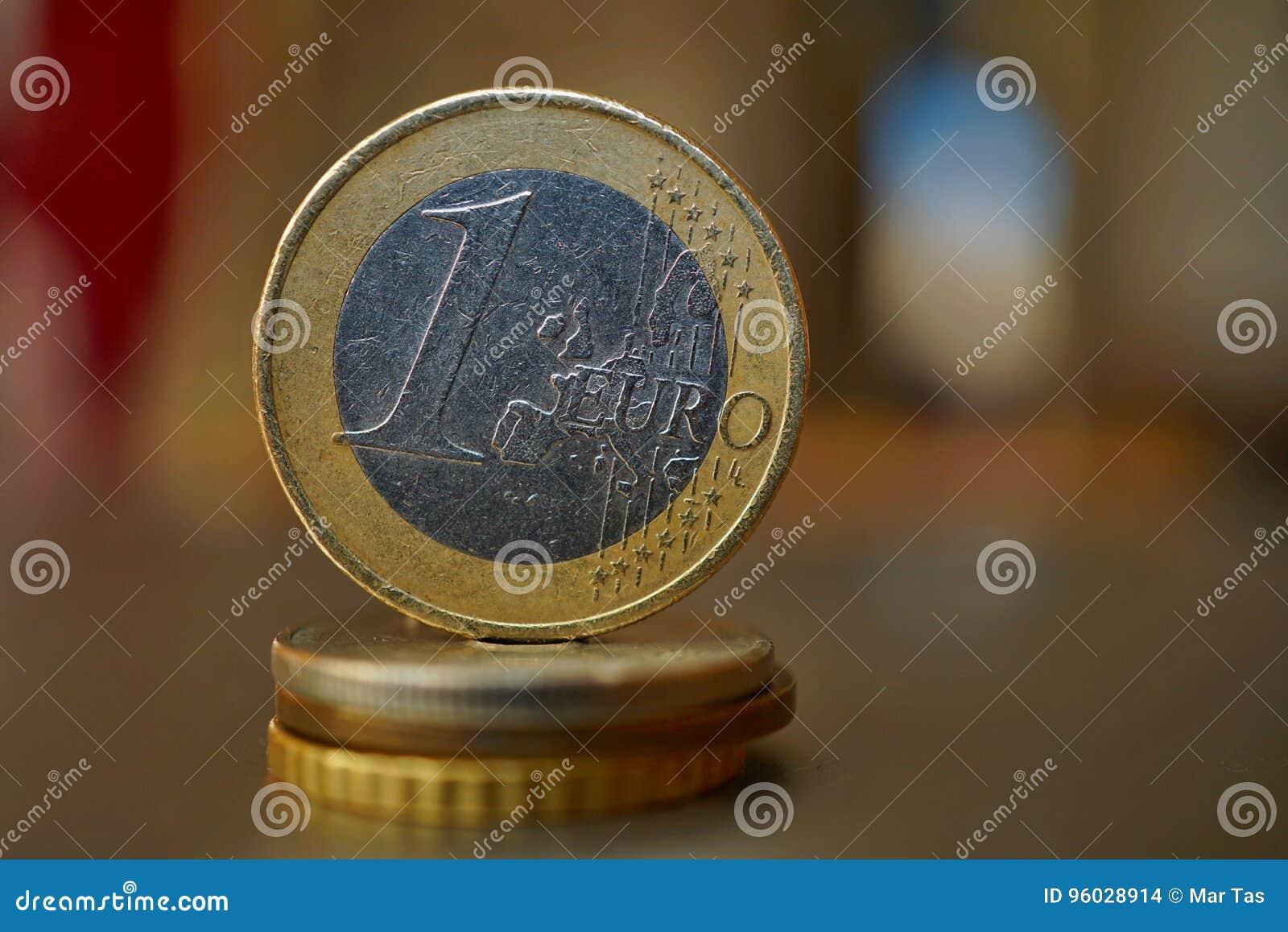 Makro- szczegół metalu euro moneta na kolumnie tworzącej monety z pozytywu ciepłym tłem