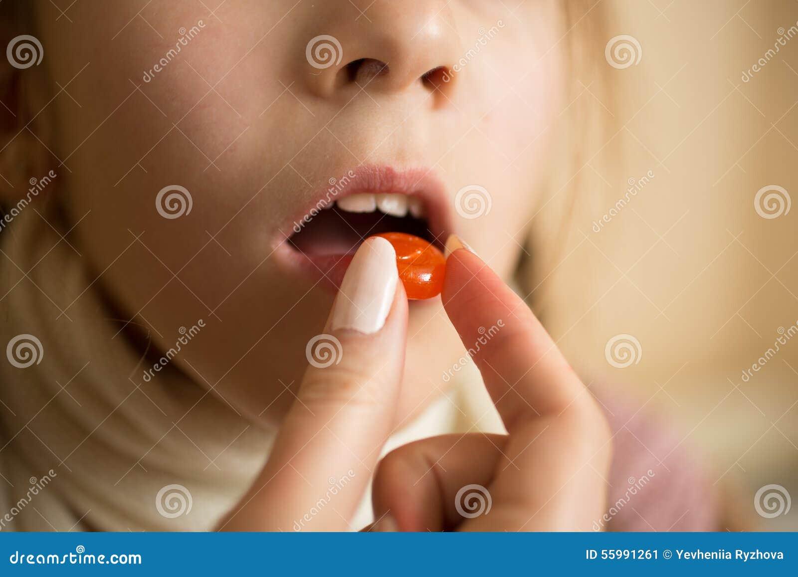 Makroschuß des kleinen Kranken mit dem Grippemädchen, das Pille im Mund einnimmt