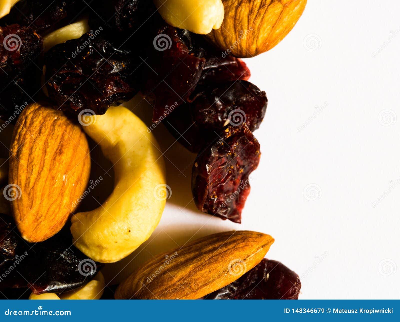 Makroschuß von Mandeln, von Erdnüssen, von Acajounüssen und von getrockneten Moosbeeren auf weißem Hintergrund mit Raum für Text-