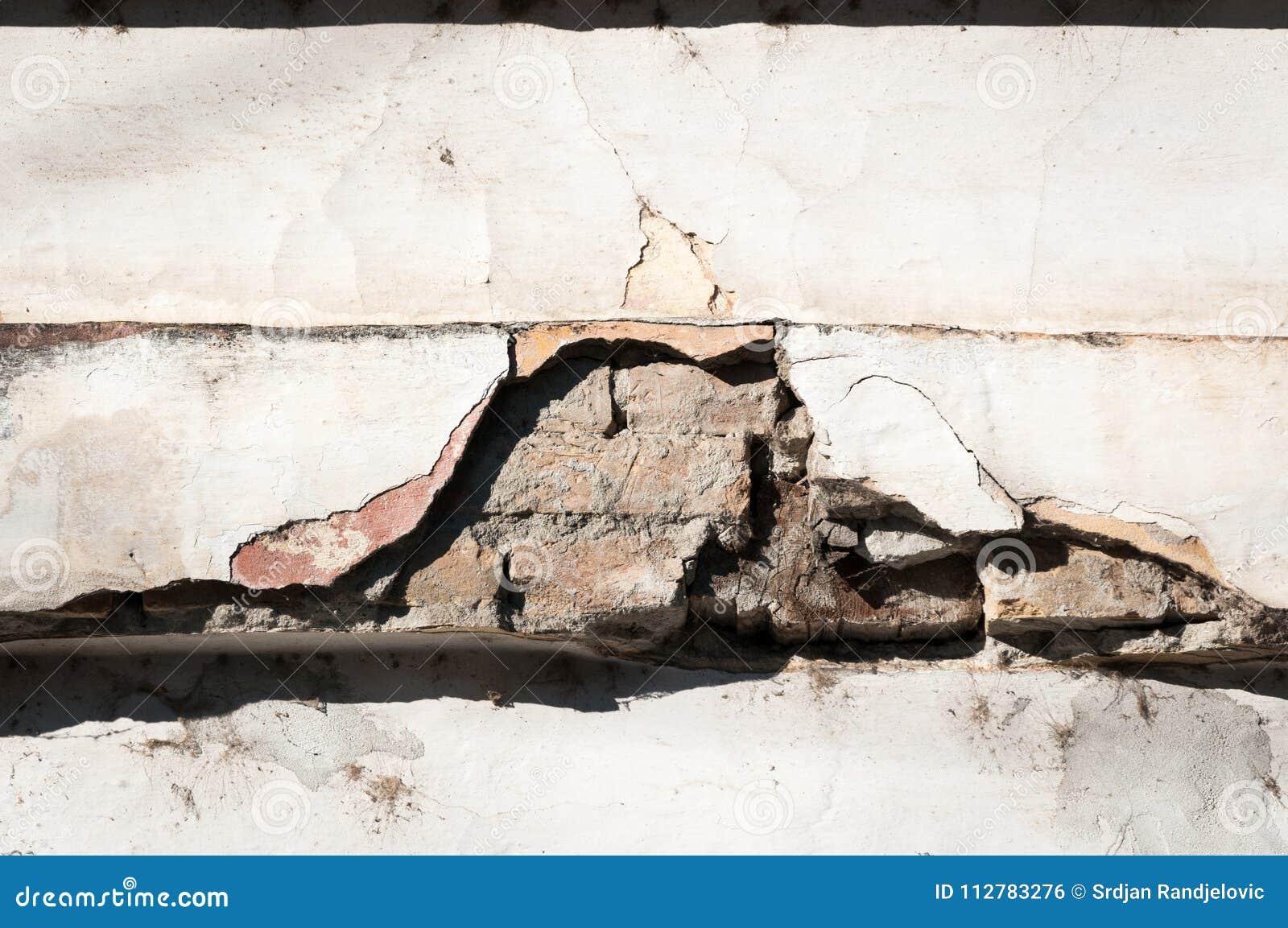 Mala base de la fundación en casa vieja o pared agrietada constructiva de la fachada del yeso con el fondo del ladrillo