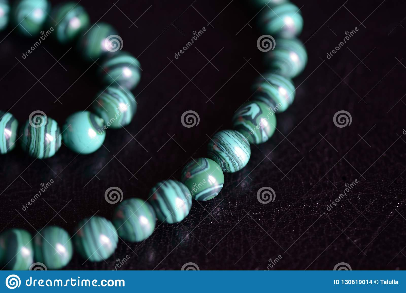 Malachite stone beads necklace on a dark background