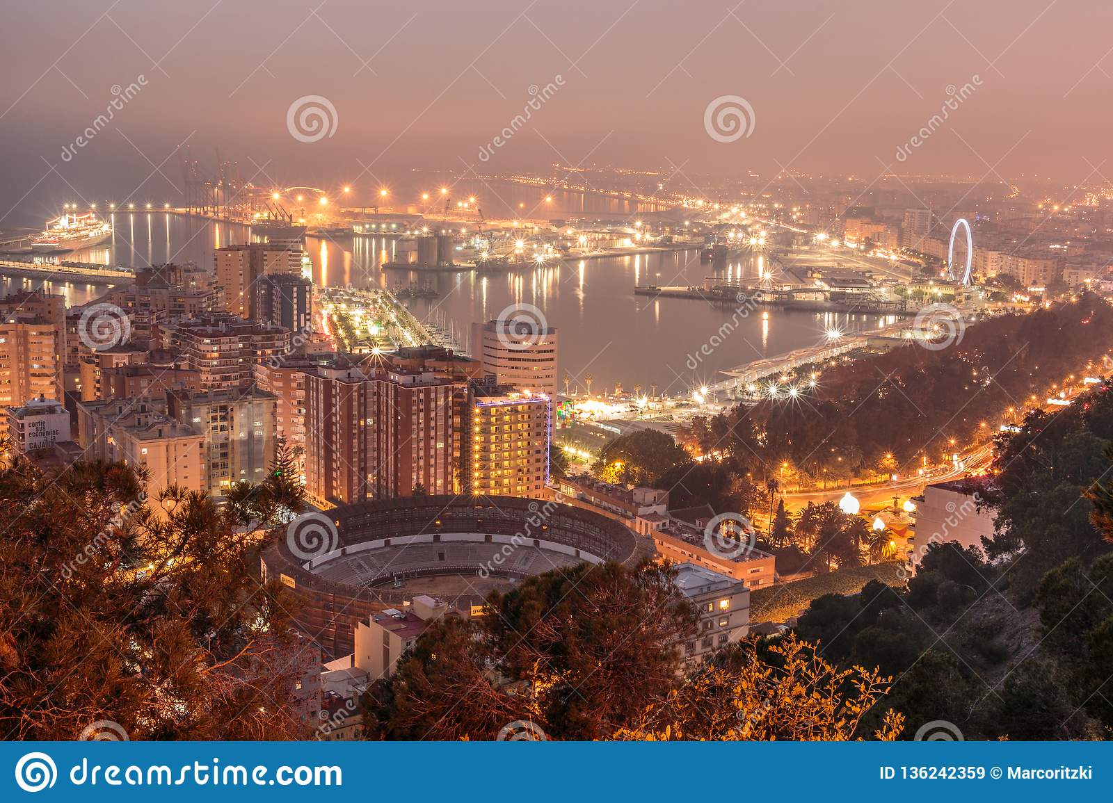 Malaga at night with harbor and ships and lighting area