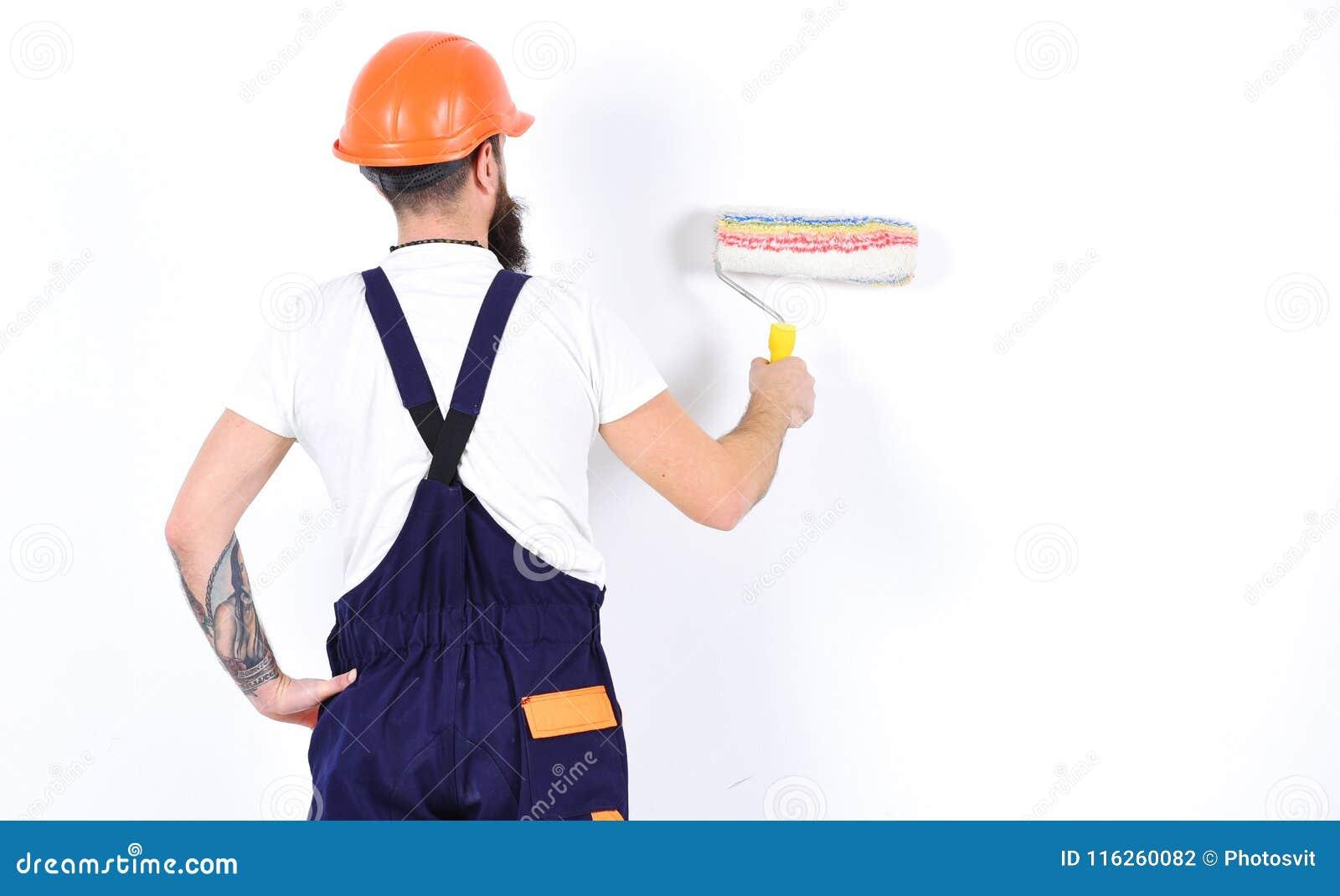 Malarz, decorator, pracownik budowlany pracuje przed biel ścianą, trzyma farba rolownika, biały tło odświeżanie