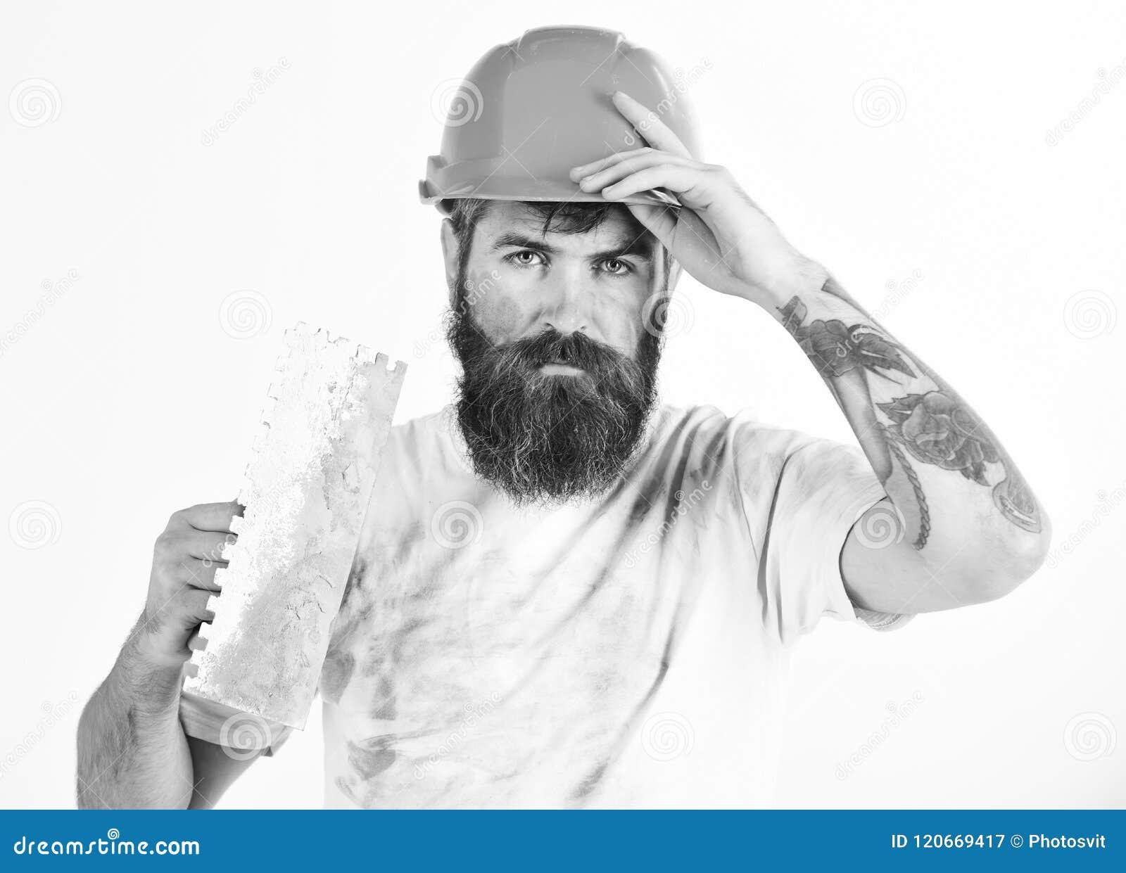 Malarz, gipsiarz, repairman, brygadier w hełmie lub ciężki kapelusz, trzymamy kitu nóż, gipsuje narzędzie Brutalny repairman