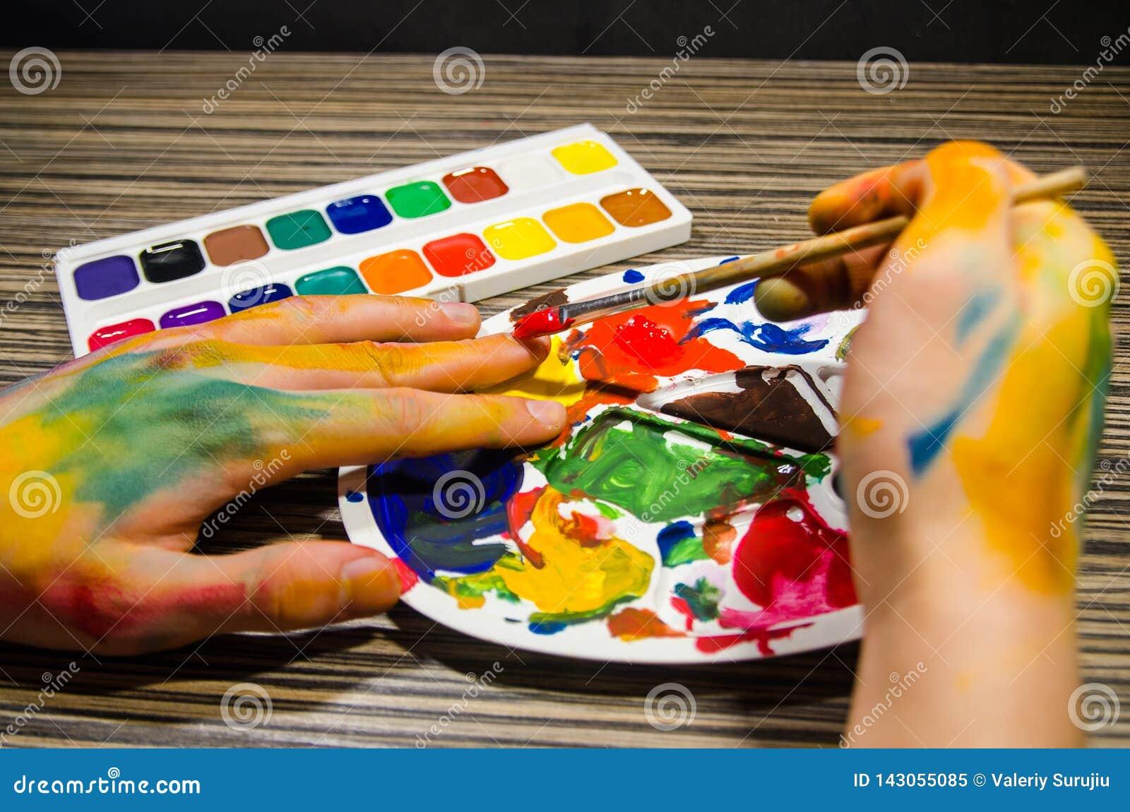 Malarz ręki robi manicure owi z czerwonym guaszem barwią