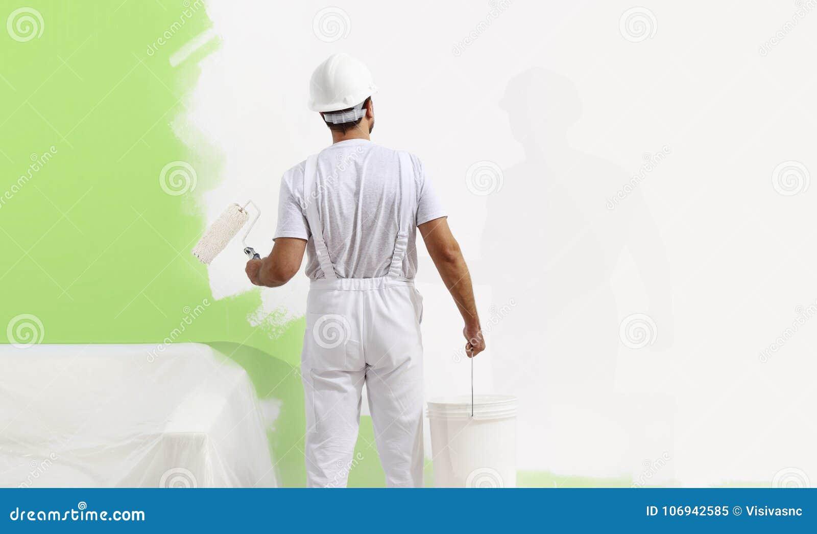 Malarza mężczyzna przy pracą z farba rolownikiem, ściennego obrazu zieleni col