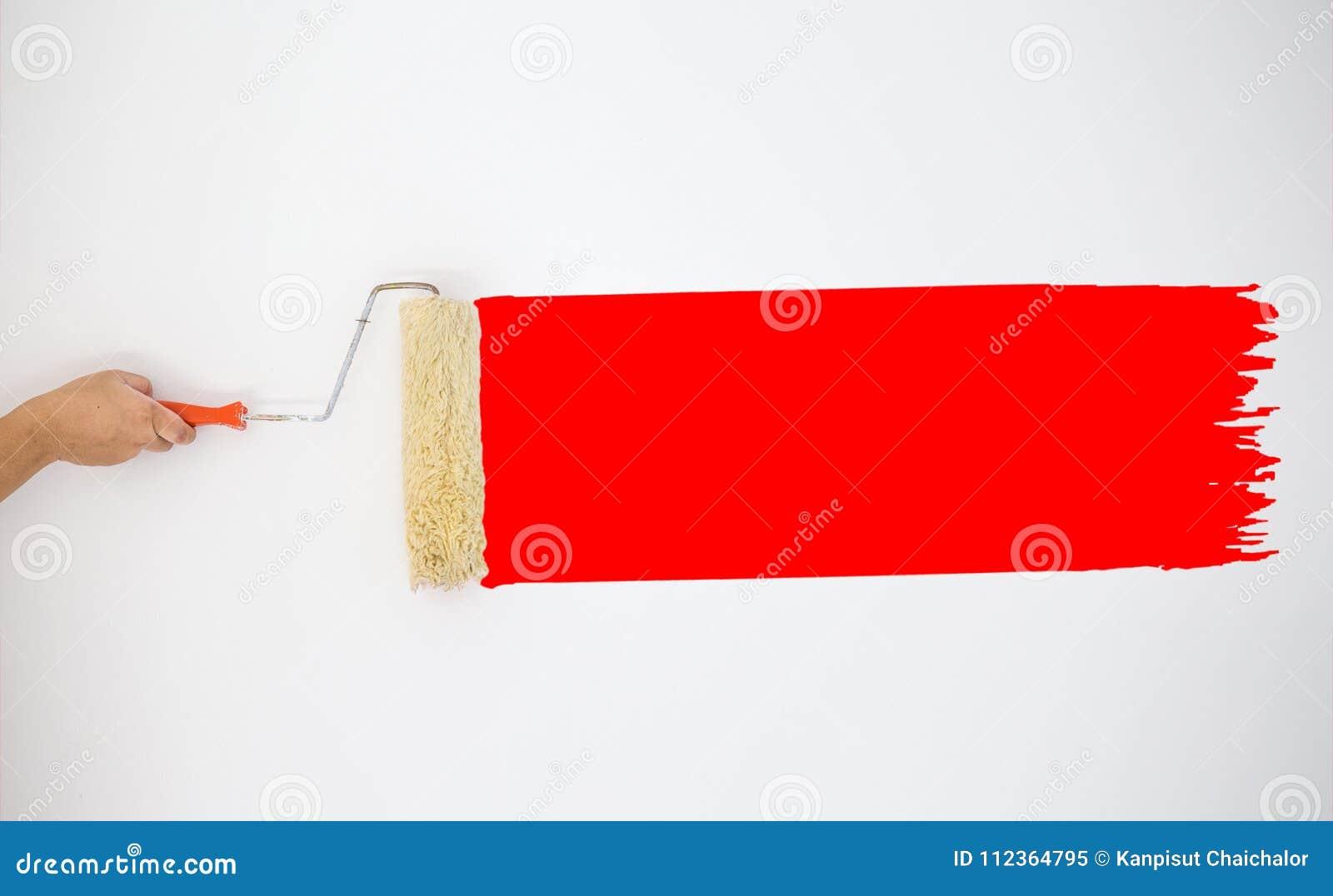 Malarza ` s ręczny rolownik malować czerwonego kolor maluje na popielatej ścianie
