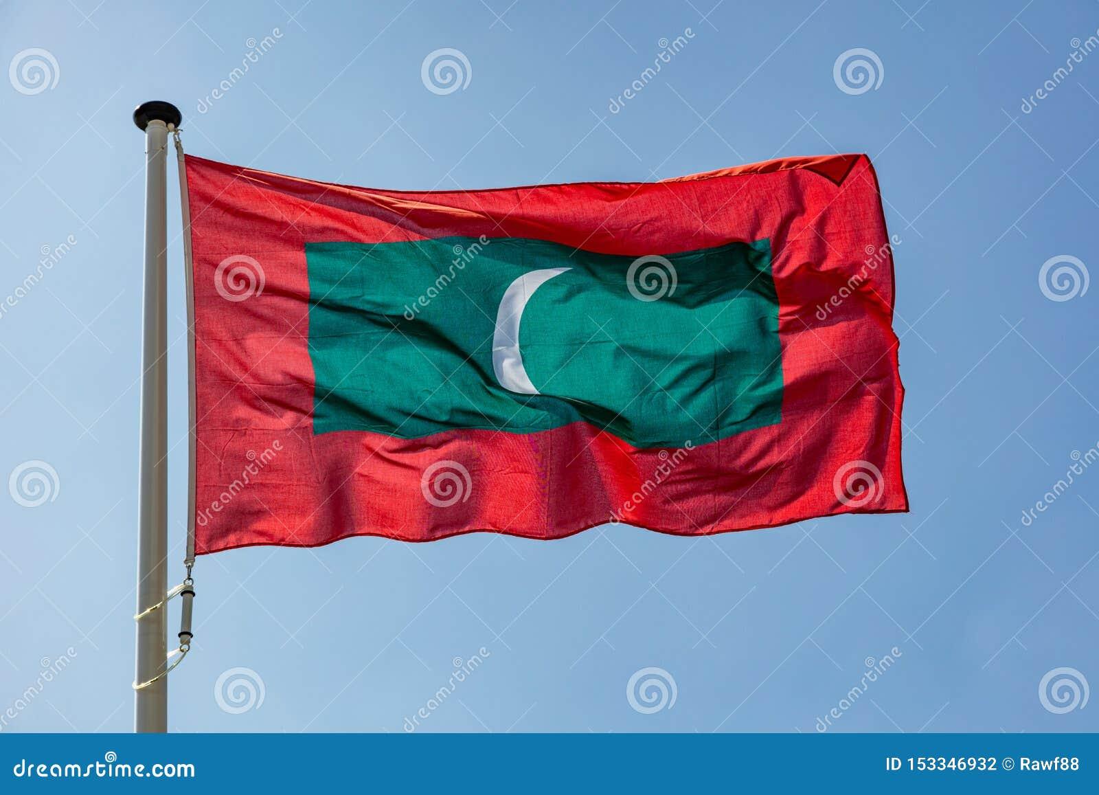 Maldives flagi falowanie przeciw jasnemu niebieskiemu niebu