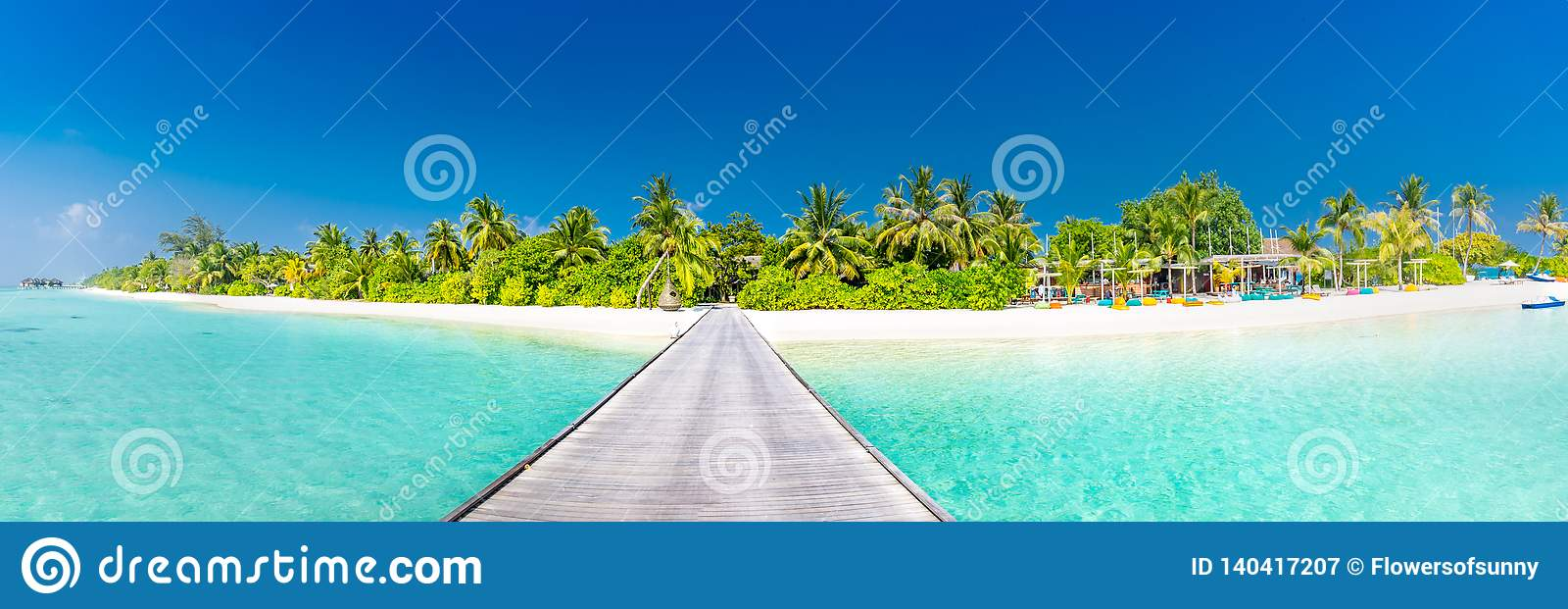 Maldives island beach panorama. Palm trees and beach bar and long wooden pier pathway. Tropical vacation and summer holiday banner