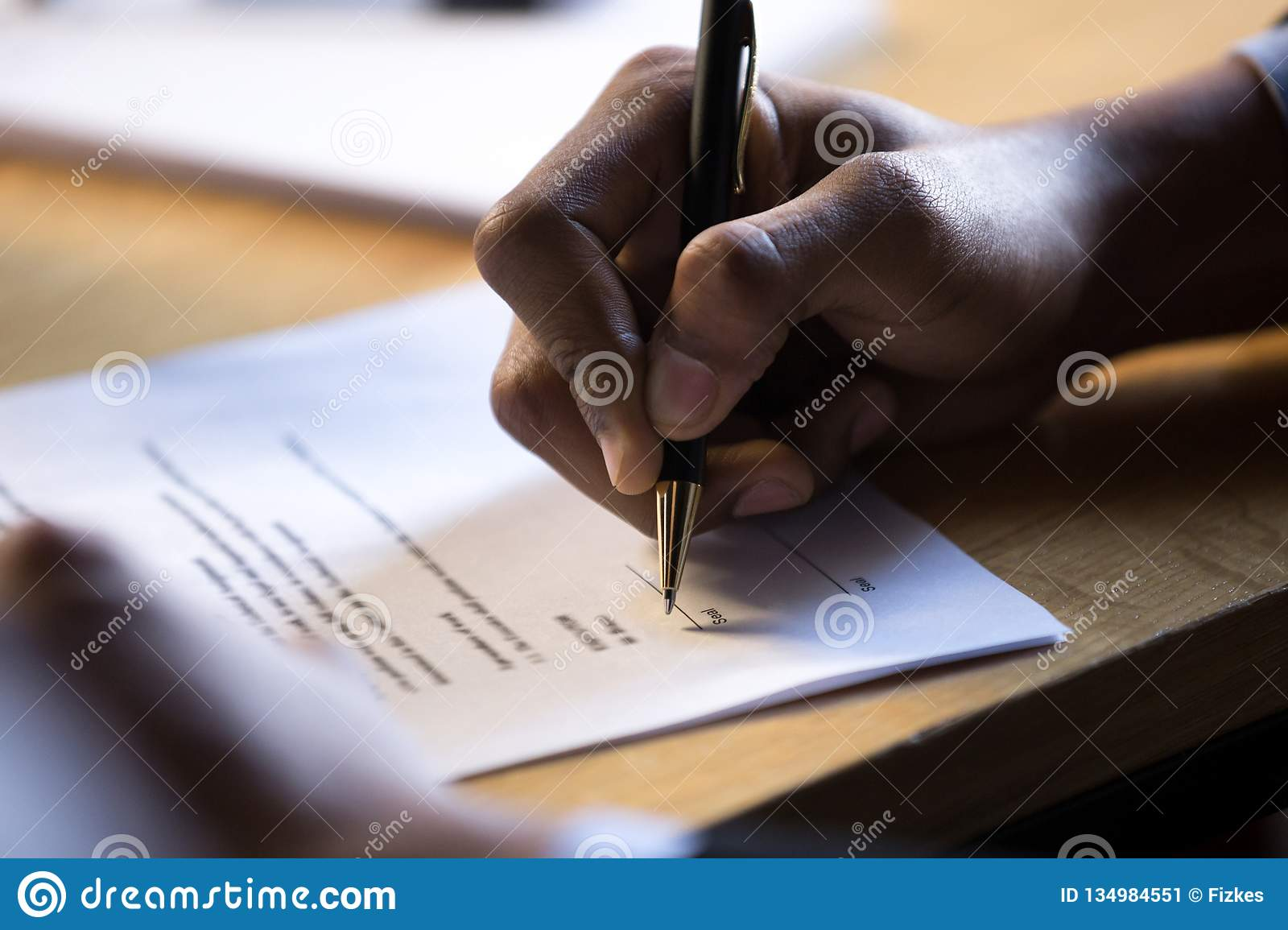 Male african hand write signature on legal corporate paper docum