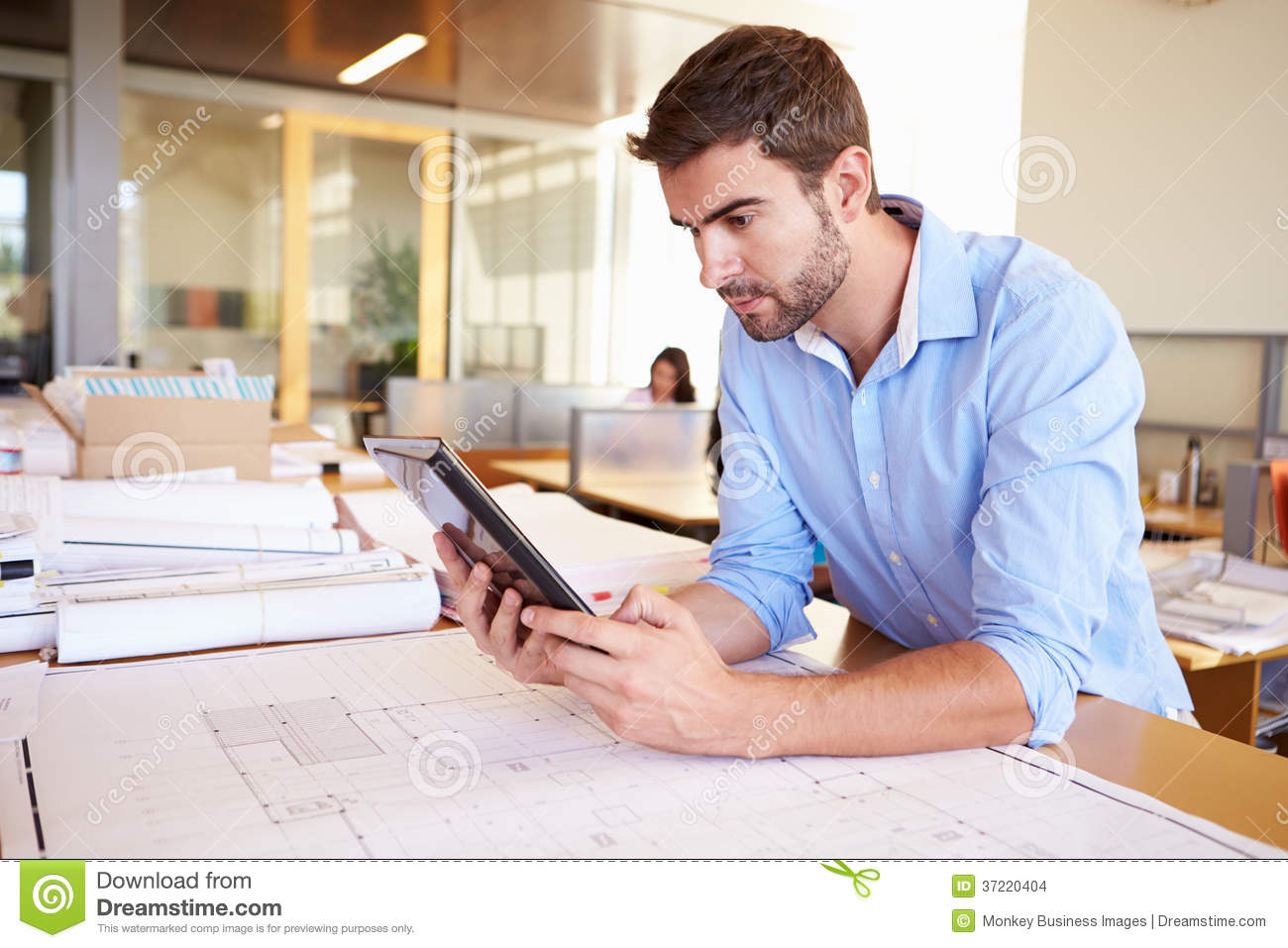 male architect with digital tablet studying plans in office stock photo image 37220404. Black Bedroom Furniture Sets. Home Design Ideas