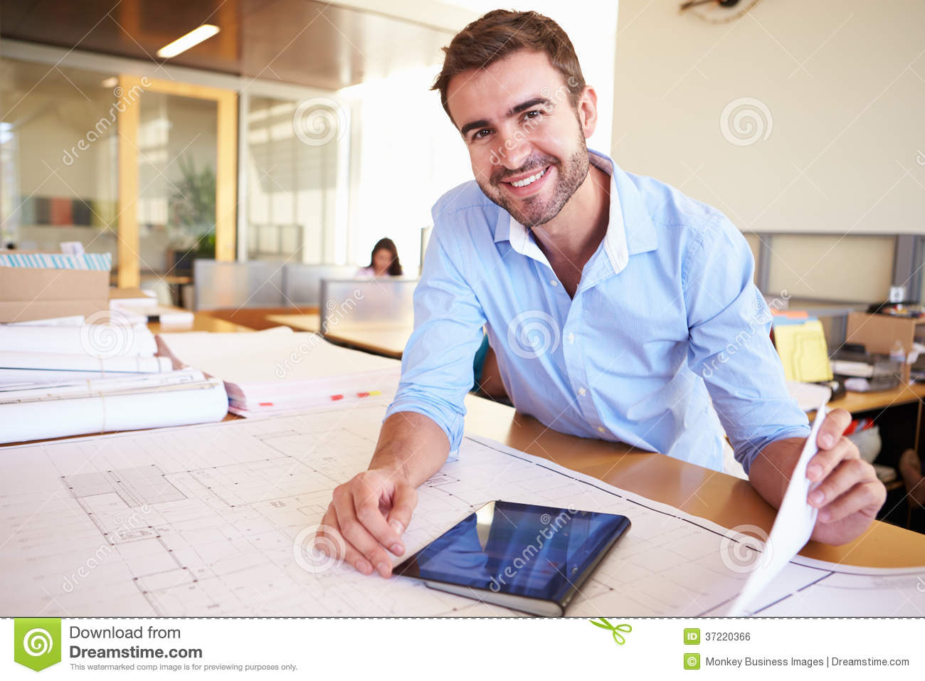 Male Architect With Digital Tablet Studying Plans In