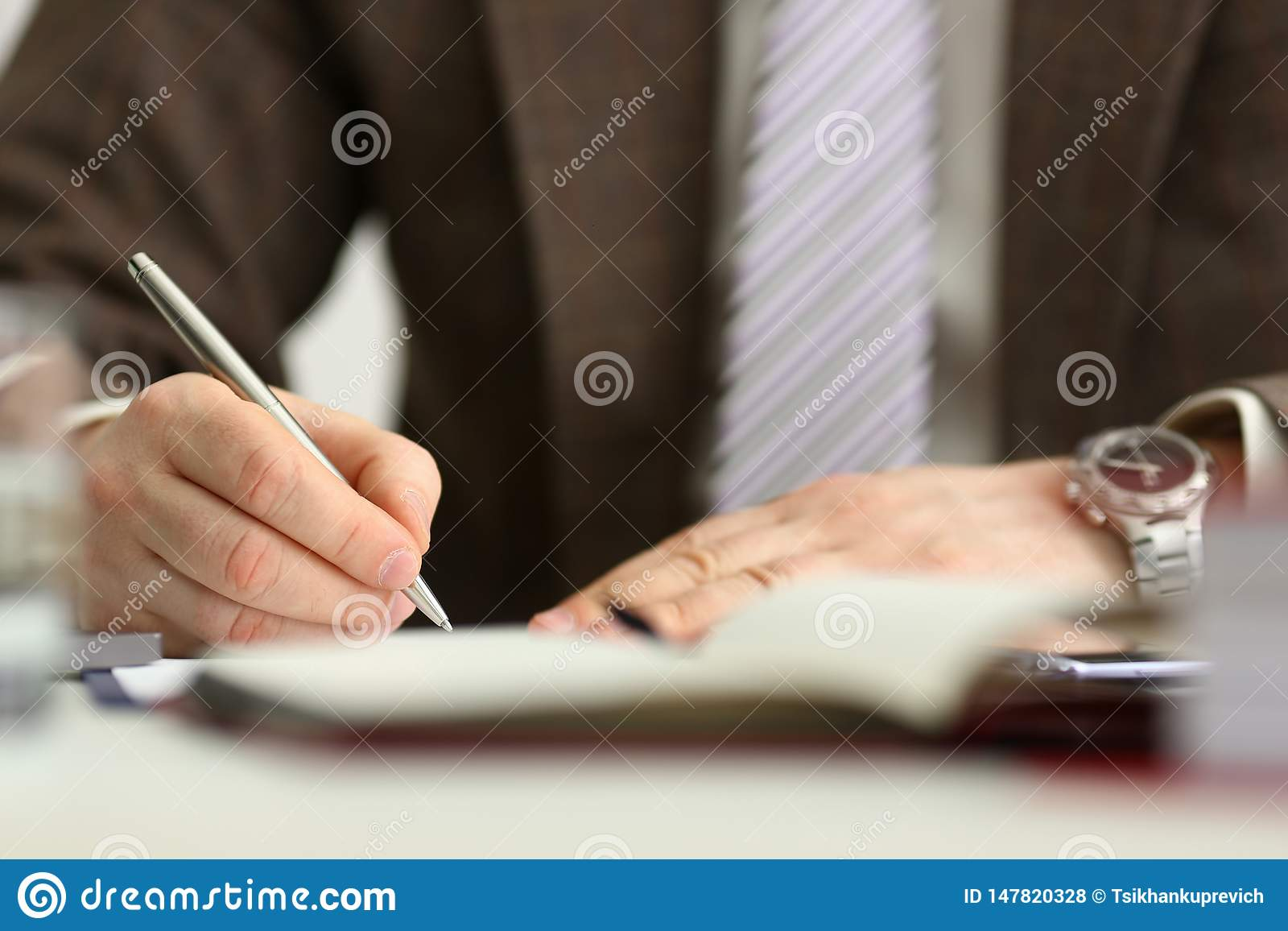 Male arm in suit and tie hold silver pen