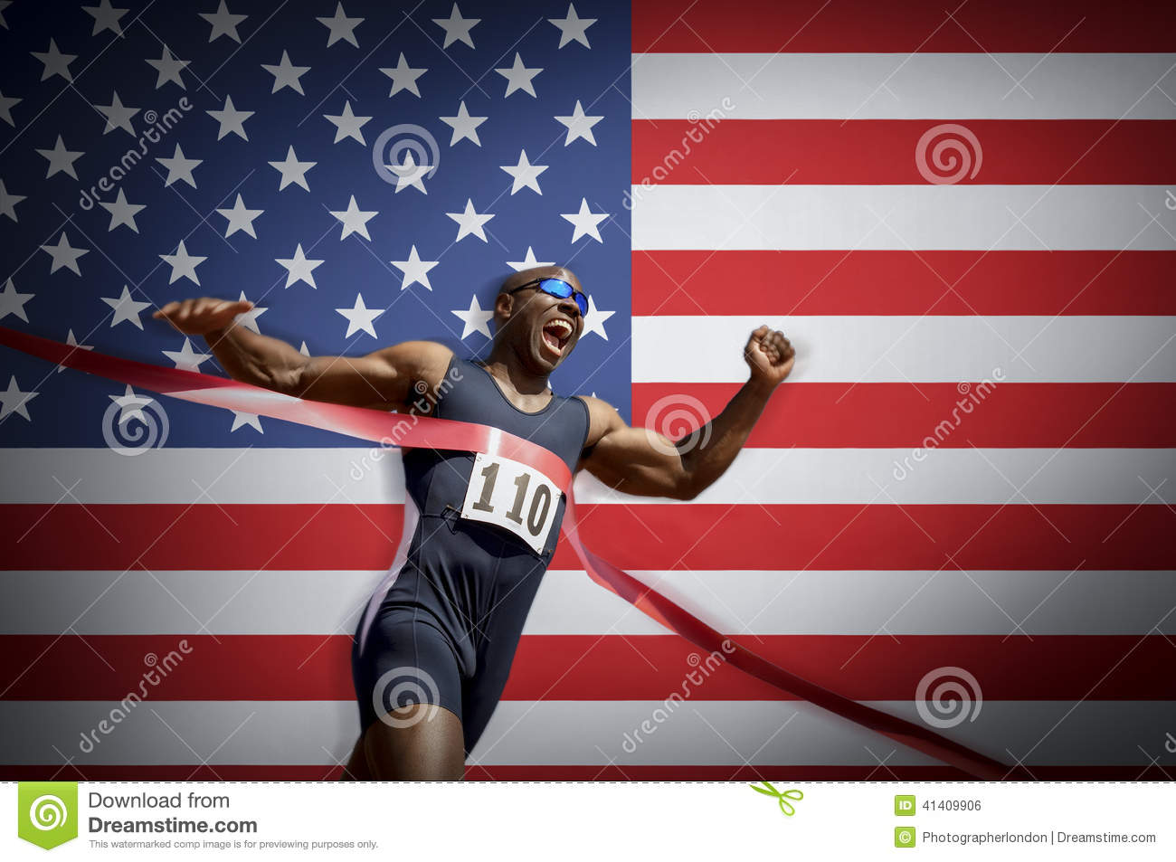 Male athlete crossing finish line against American flag