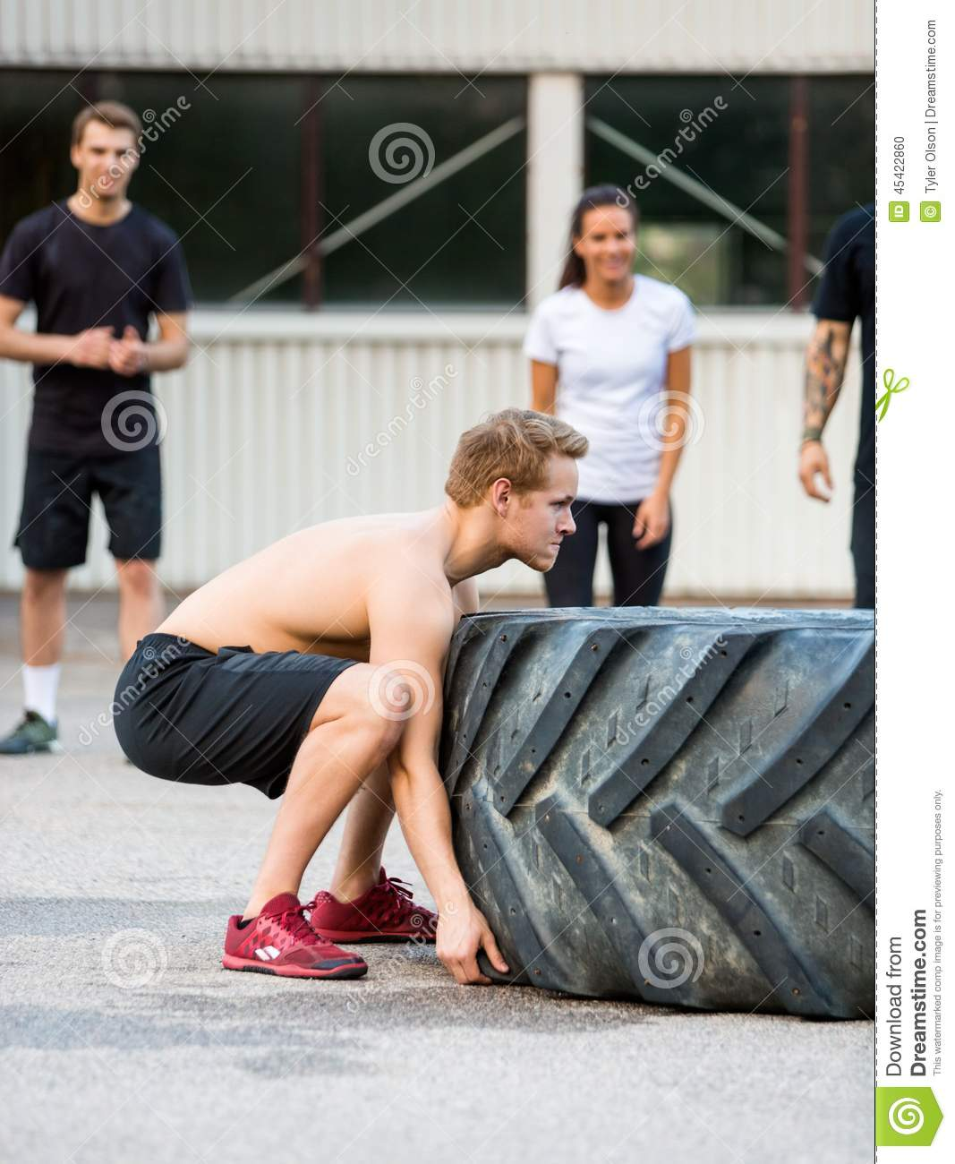 Amino Z Team Womens Weight Lifting Bodybuilding Gym: Male Athlete Flipping Tractor Tire Stock Photo