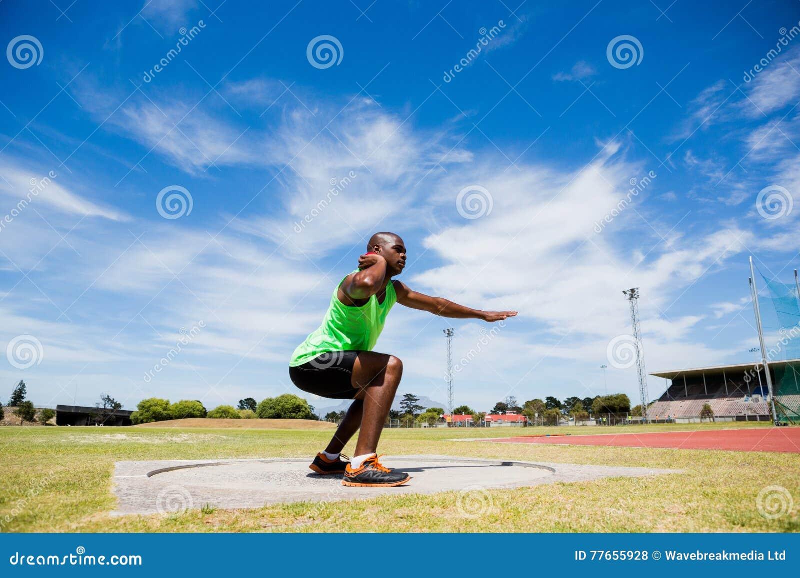 Male athlete preparing to throw shot put ball