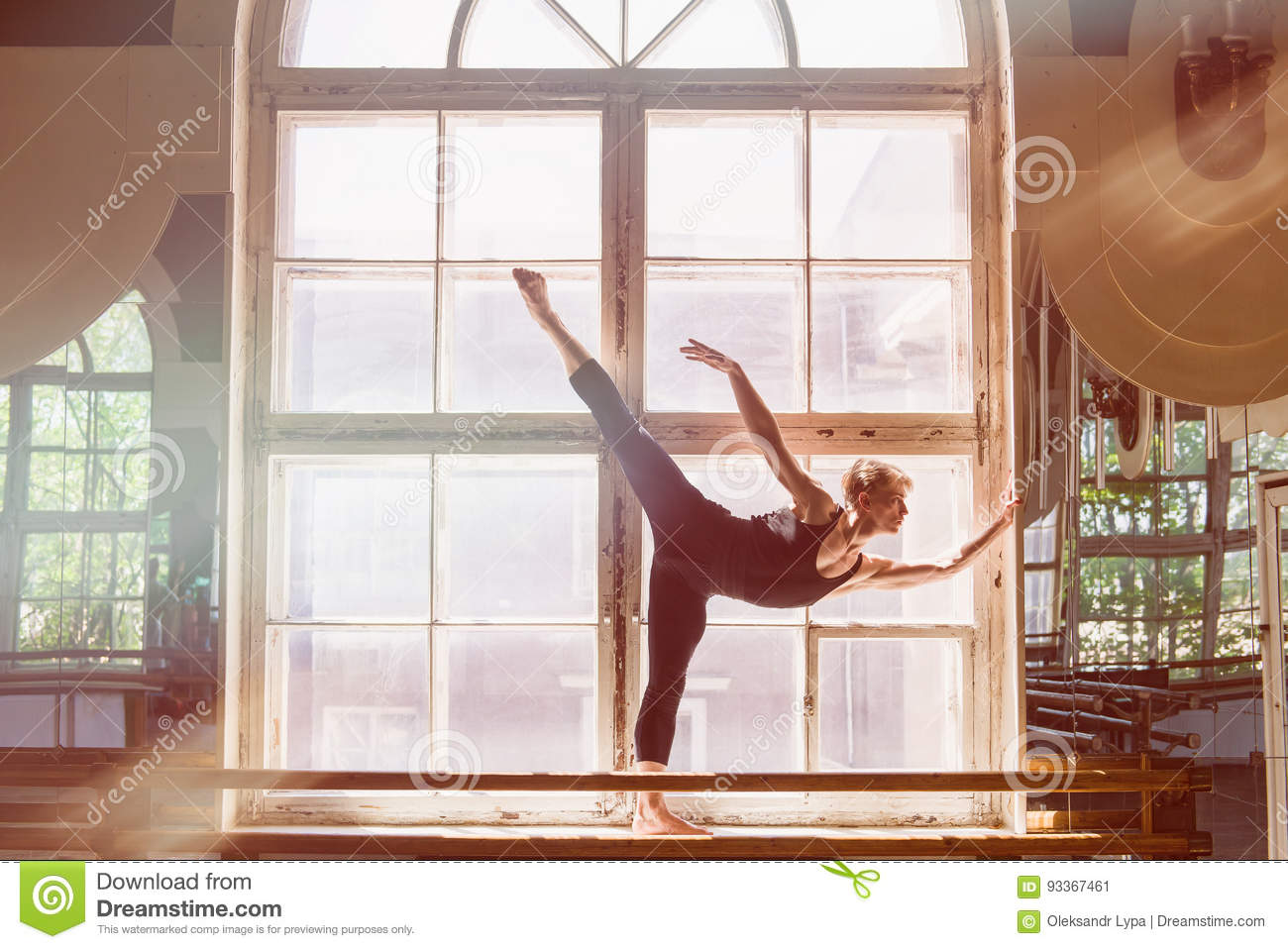 Male ballet dancer is dancing in front of a window