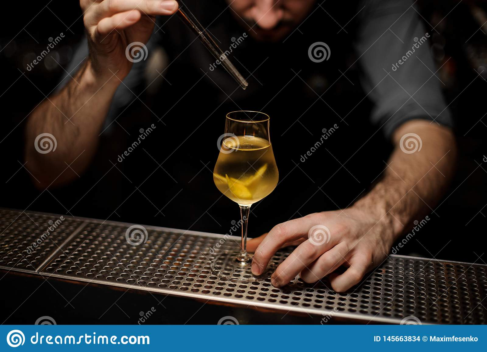 Bartedner adding lemon rind with forceps in cocktail