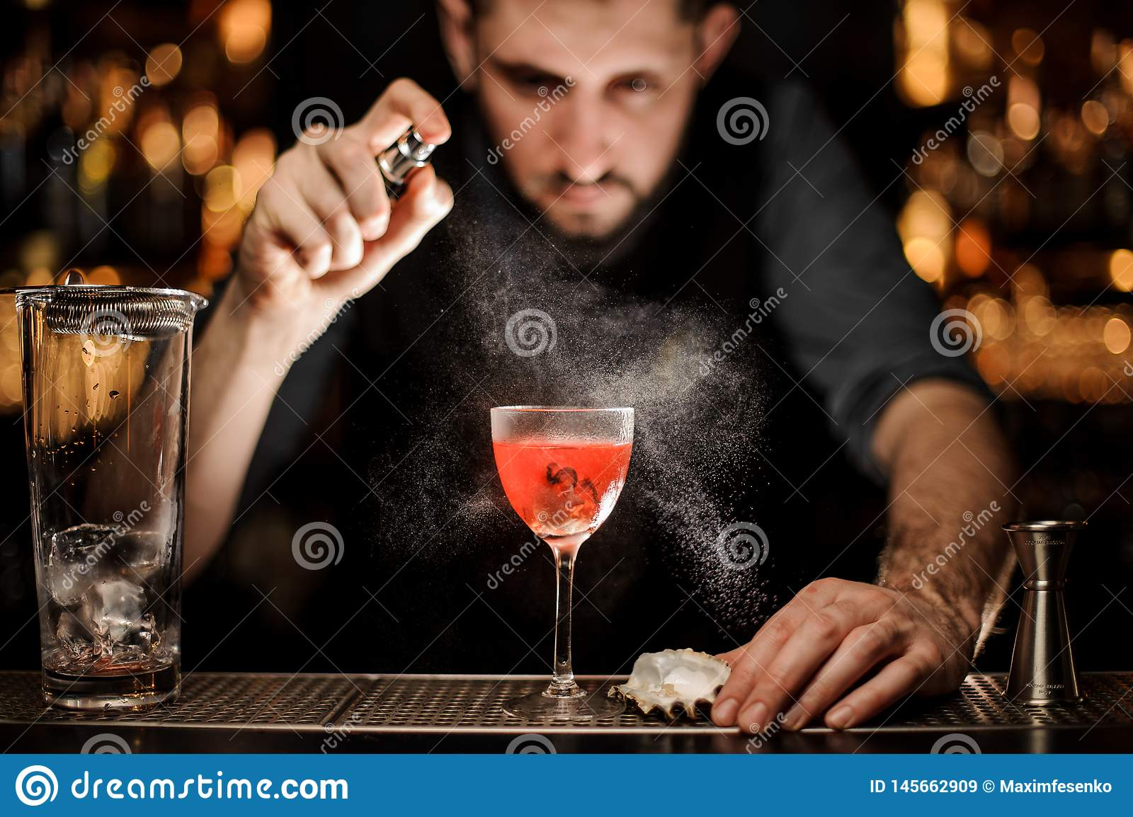 Bartender pours an alcohol cocktail using sprayer