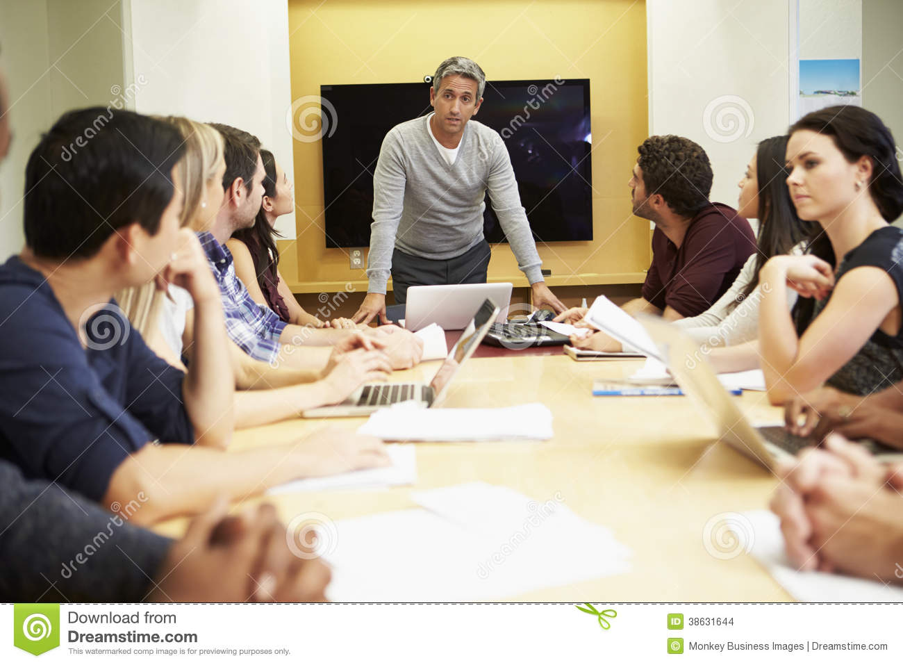 Male Boss Addressing Meeting Around Boardroom Table Stock