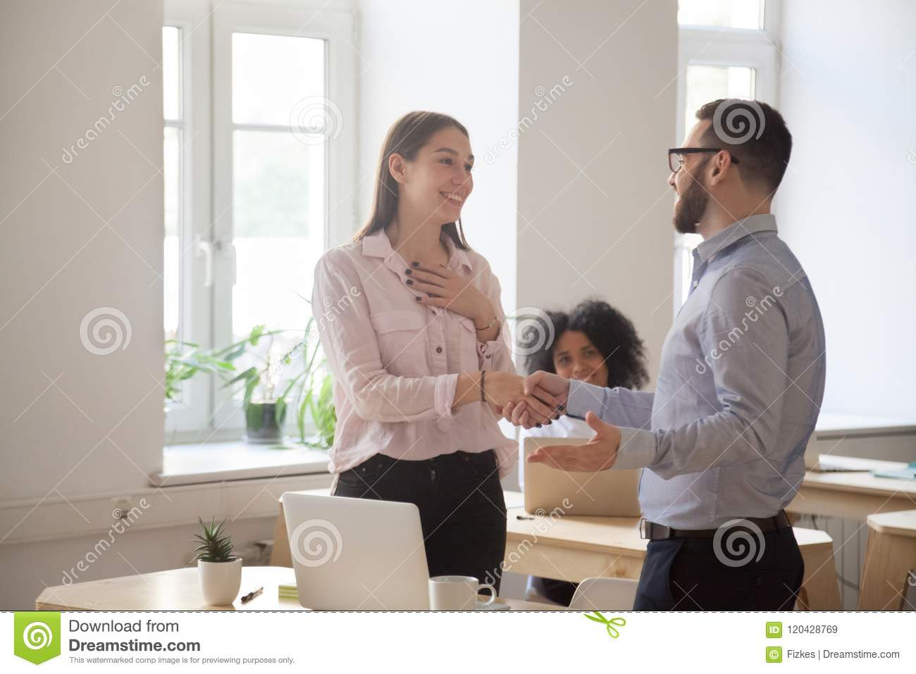 Male boss handshaking employee congratulating with promotion