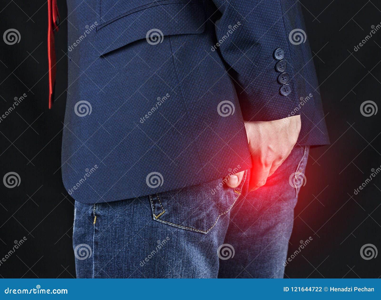 Male businessman holding his ass, hemorrhoids
